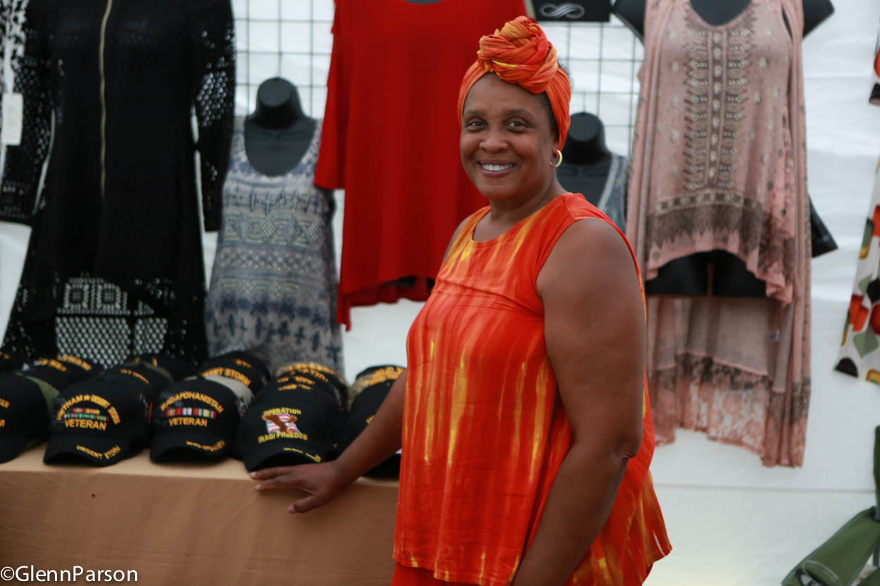 Woman proudly displaying caps in Vendor Marketplace