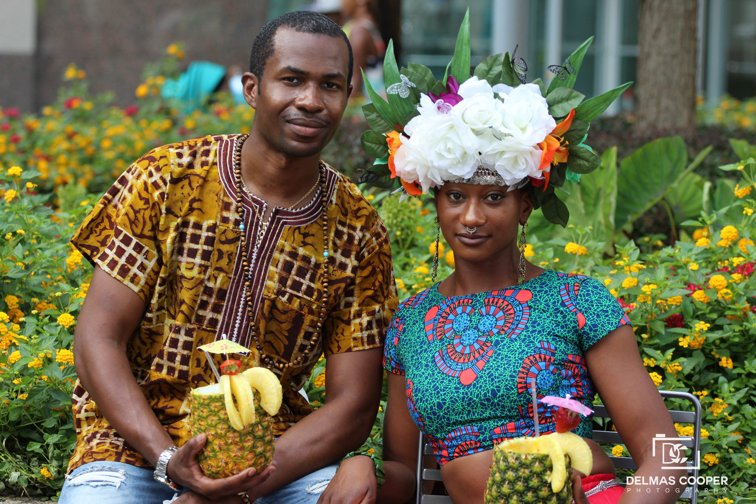 Man and woman in African print clothing with pineapple drinks