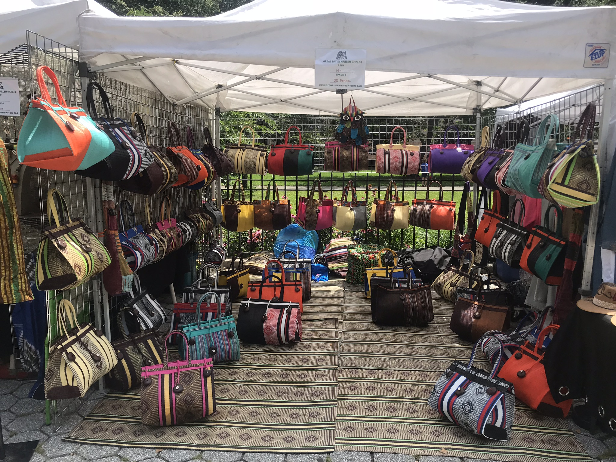 recycled handbag artist Adama Sylla's booth showing many colorful bags