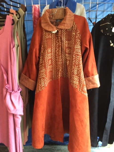 Women's long copper colored coat printed with Adinkra symbols