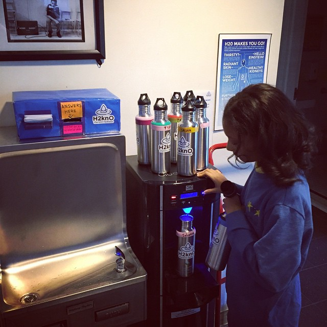 A Water Champion filling up her classes water bottles.