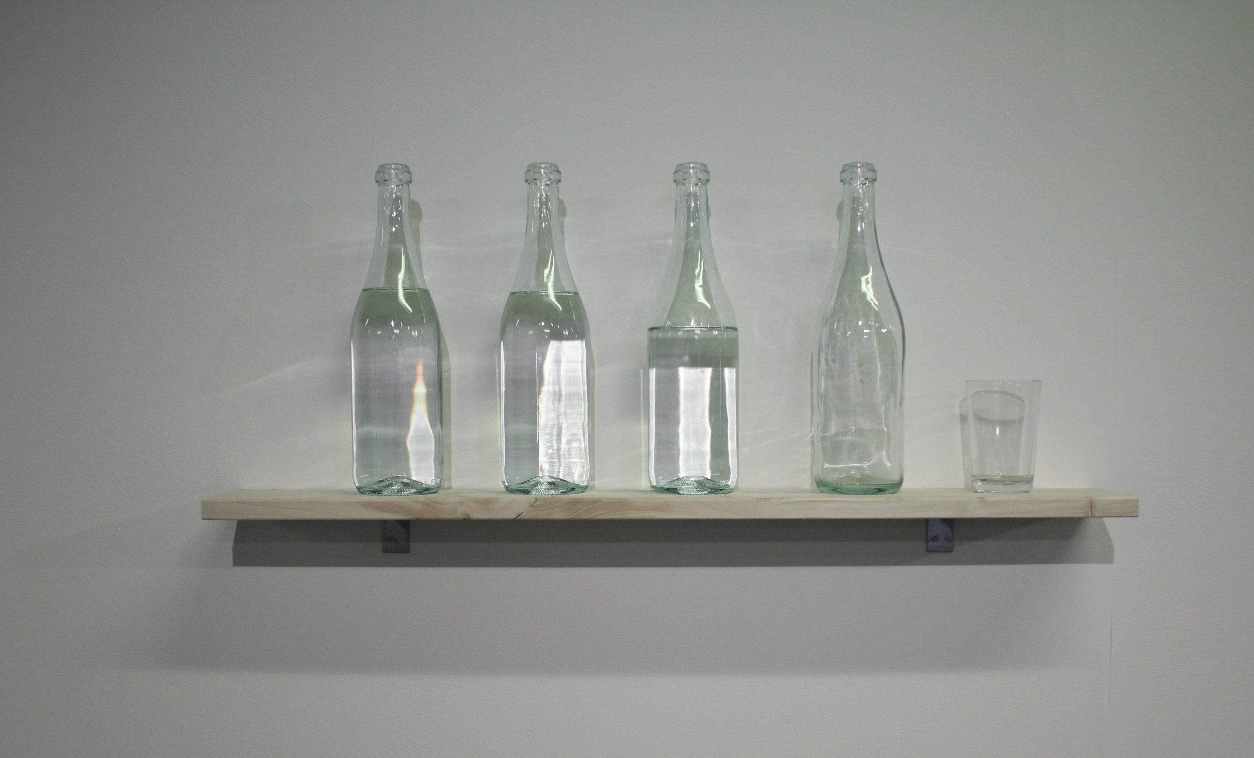 Kusettaa  2017  lasipullot, vesilasi, vesi ja hylly