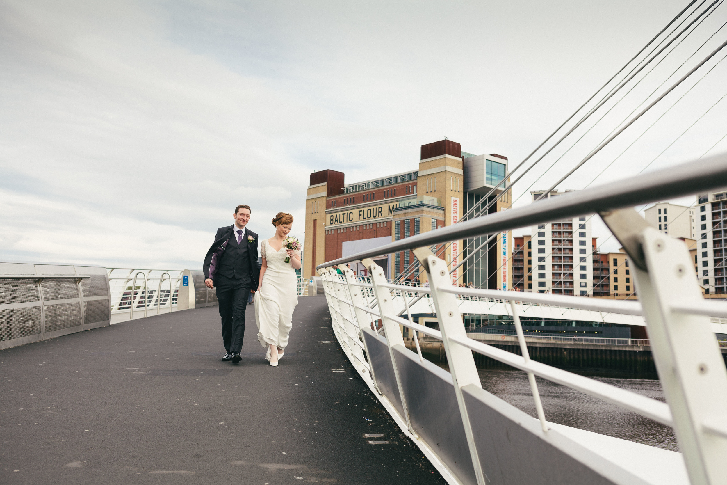Katy & Chris walking over the Millennium Bridge on Newcastle Quayside