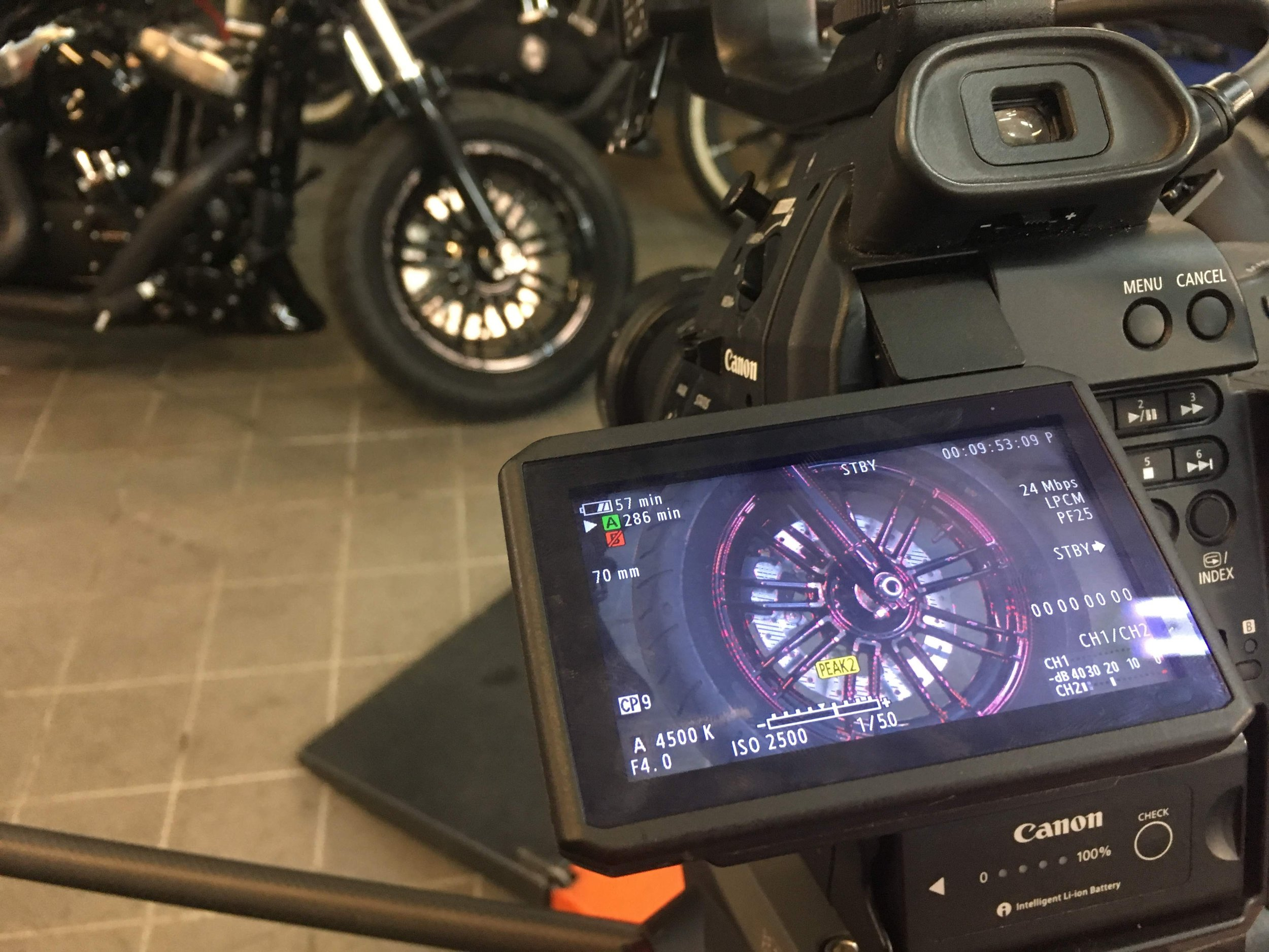 Professional video camera pointing at motorcycle wheel