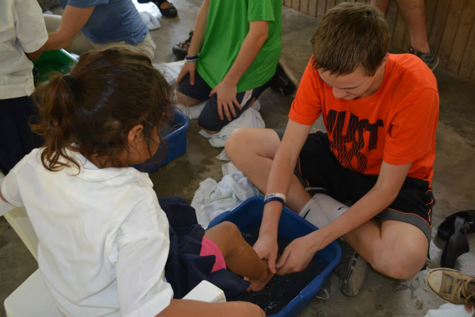 Max washing a child's feet as an act of service before receiving brand new shoes.