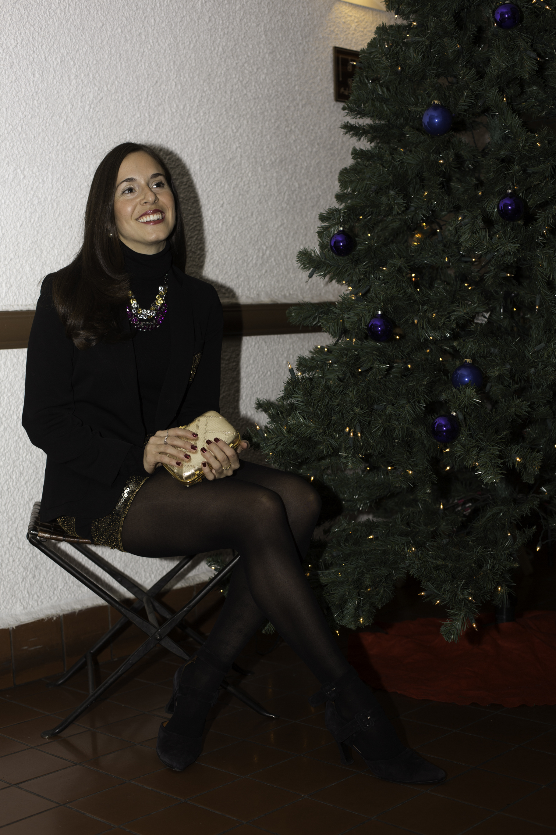 Sitting by the tree at a holiday party wearing my  Ralph Lauren  black with gold crest blazer, a  Zara  black turtleneck, gold  Topshop  sequin mini skirt, black tights, and vintage black suede pumps. My gold clutch is a  Coach  python holiday clutch. Photography by  Francisco Graciano .
