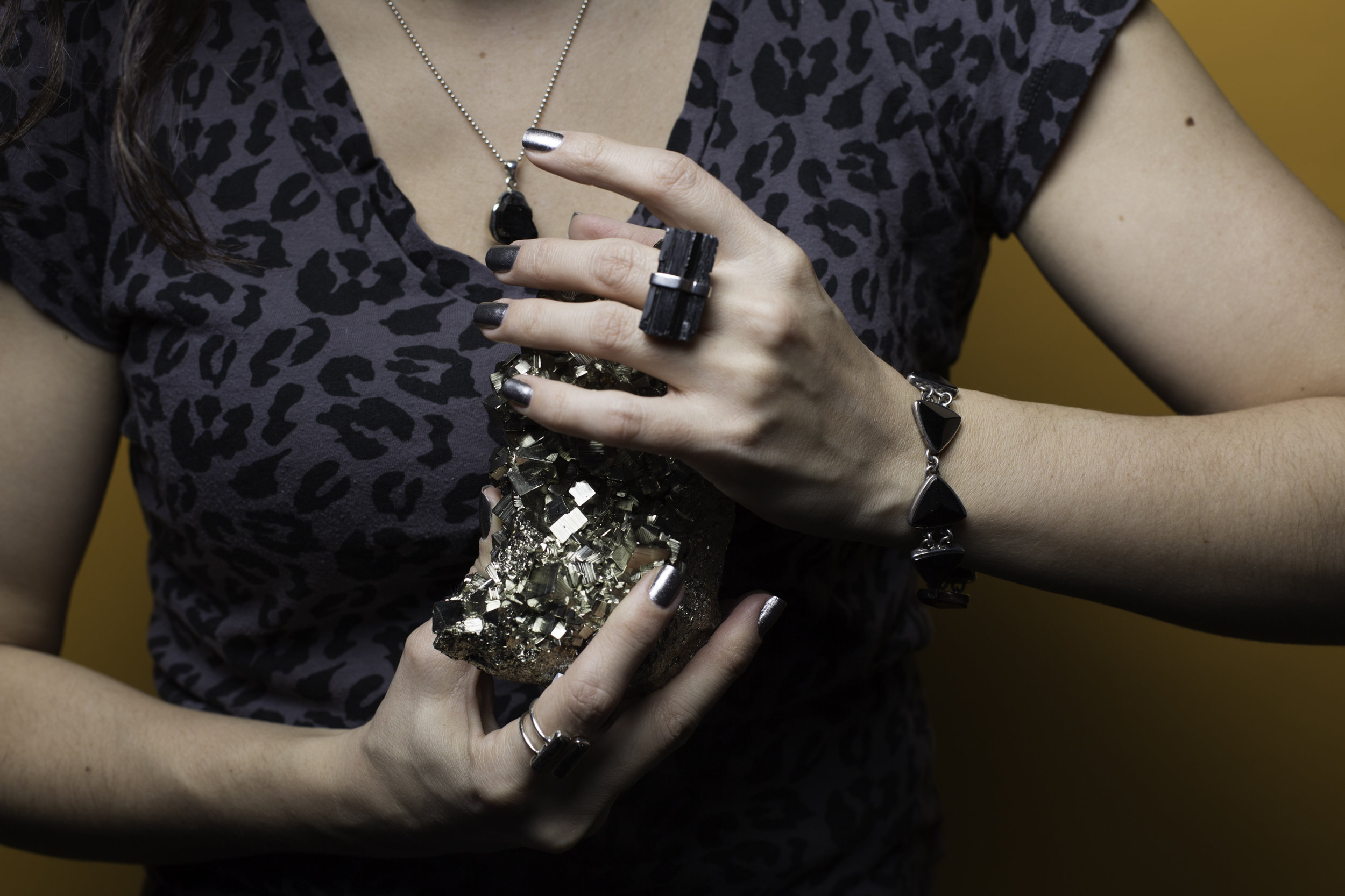 Wearing Made in Earth CollectionBlack Tourmaline Pendant, Black Tourmaline Open Front Ring (on my right hand), Black Tourmaline Ring (on my left hand), Black Tourmaline Bracelet, and I'm holding a Pyrite Cluster. Please see below for the energetic properties of the stones.