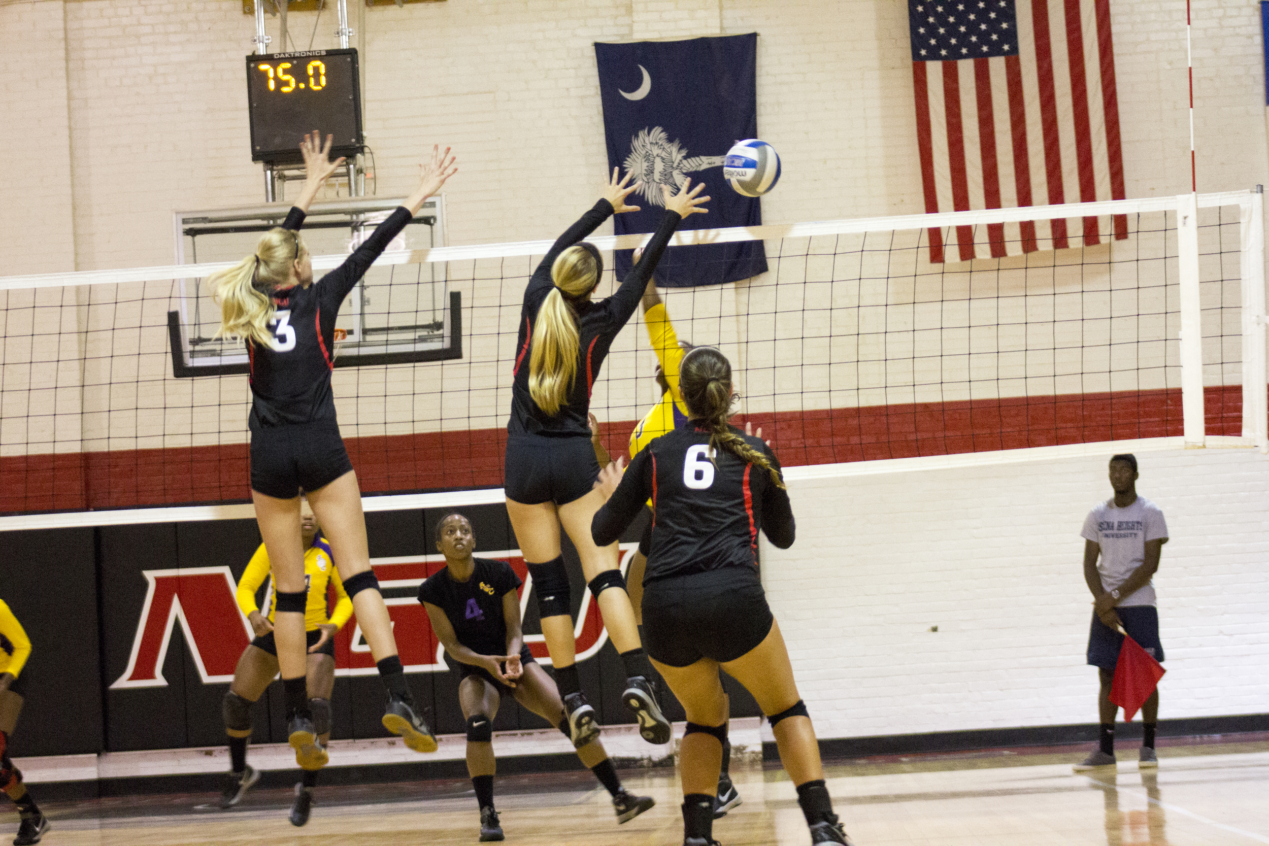 Sophomore Rachel Burts and junior Taylor Dupes stretch to block a spike.