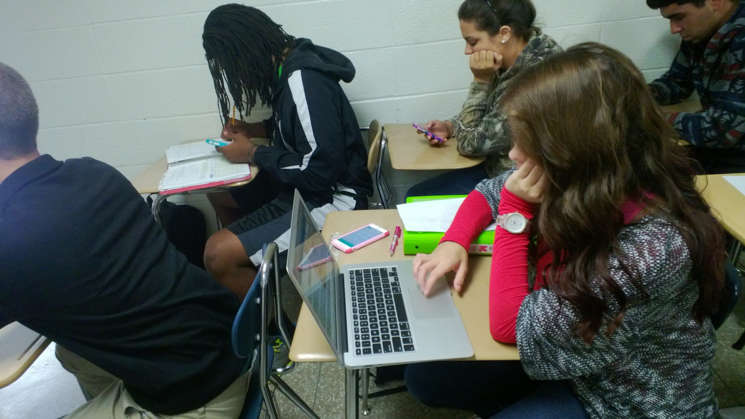 Freshman Danielle Berry (bottom right) sits on her computer in class.