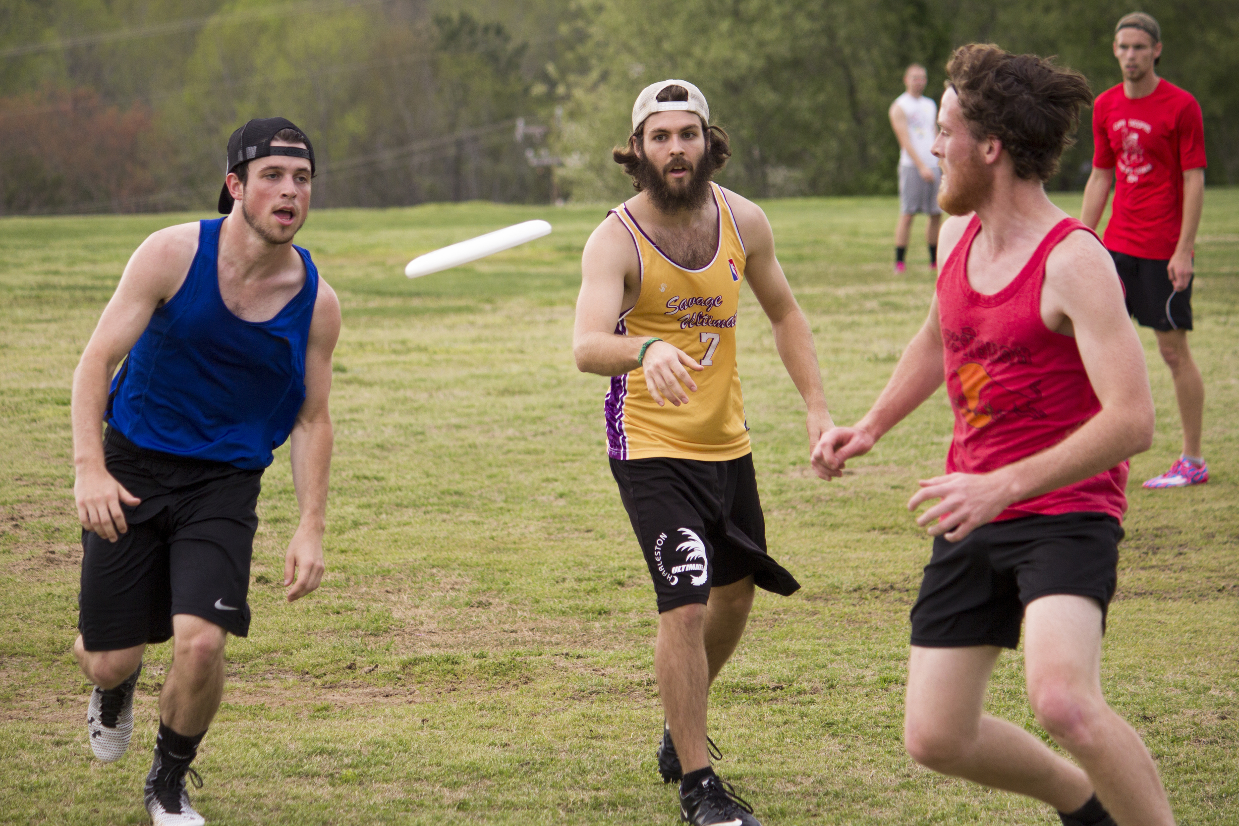 Three players race to the frisbee to obtain possession of it for their team.
