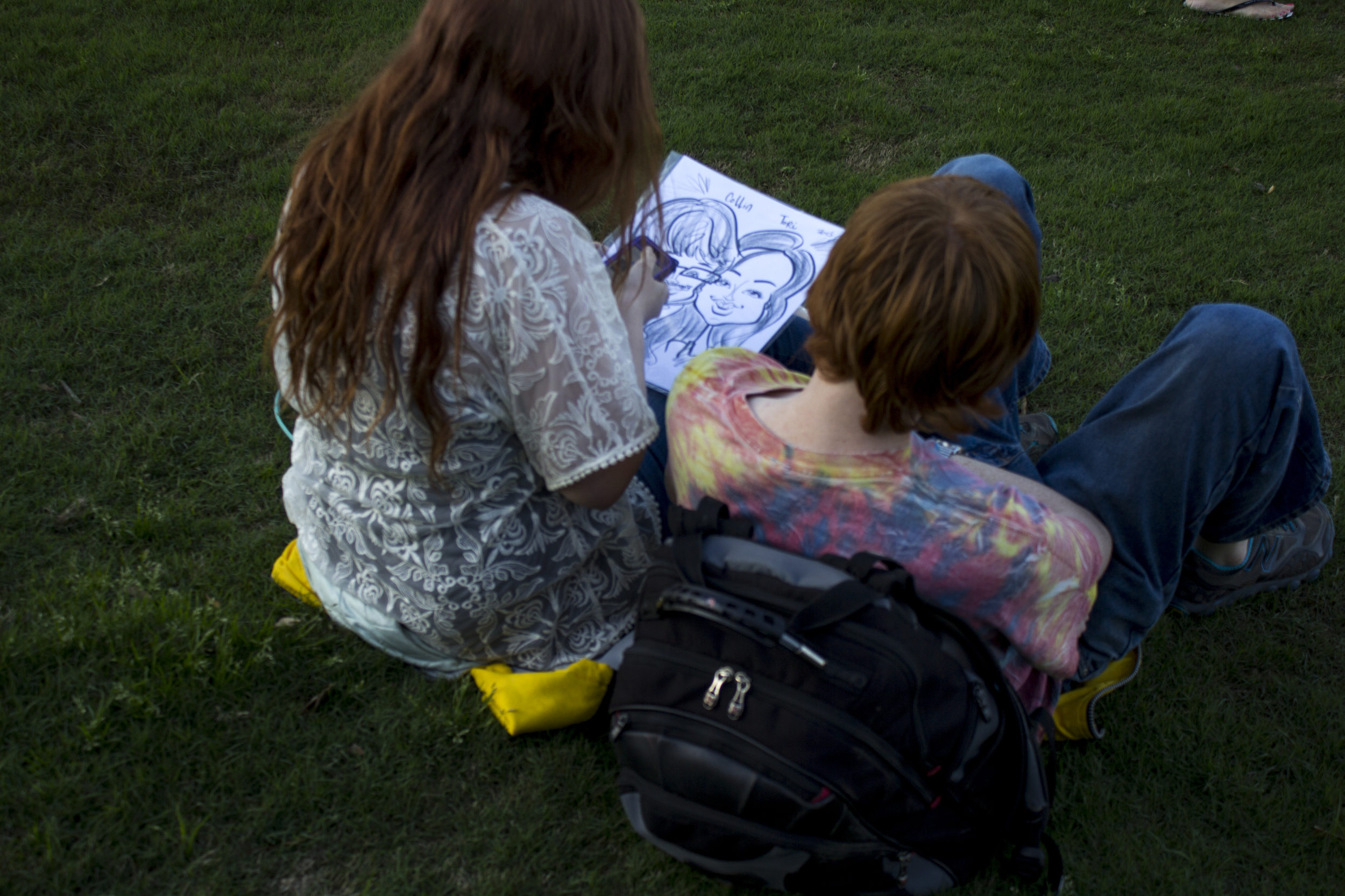 These two students enjoyed sitting in the grass after getting their own caricature drawn.