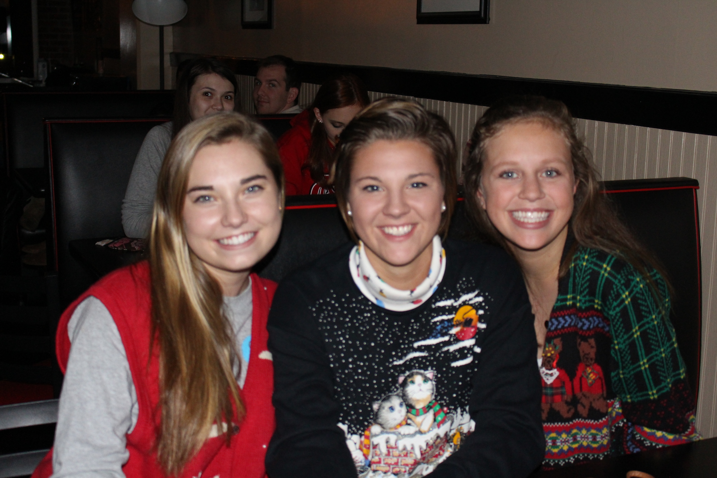 "Olivia Hayes, Rebecca Watson and Siera Blackbird showing off their ""Ugly Christmas sweaters"" during the coffeehouse."