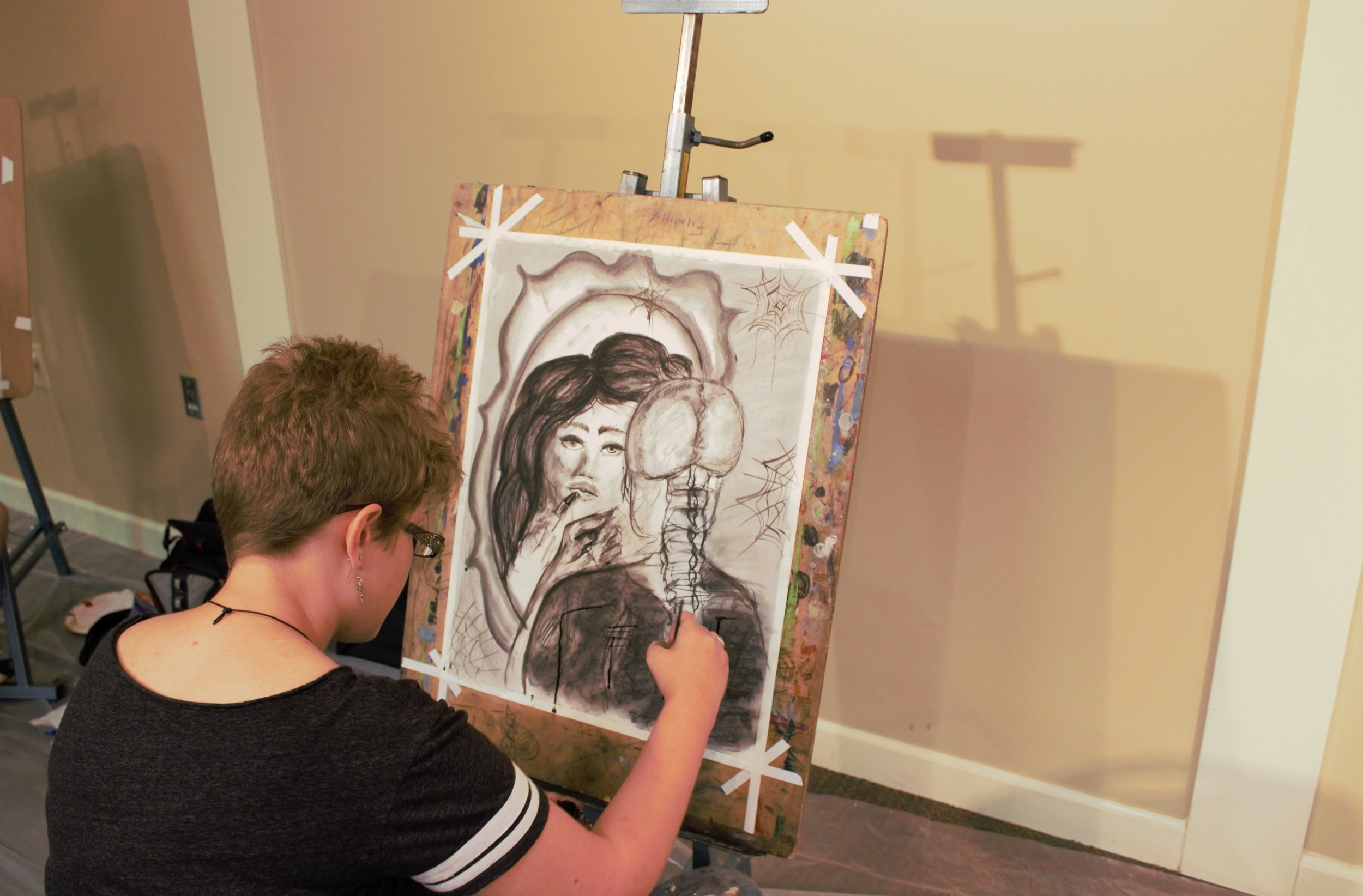Linnea Stevens concentrates on her charcoal drawing for the artist prompt during Art and Poetry Slam night.
