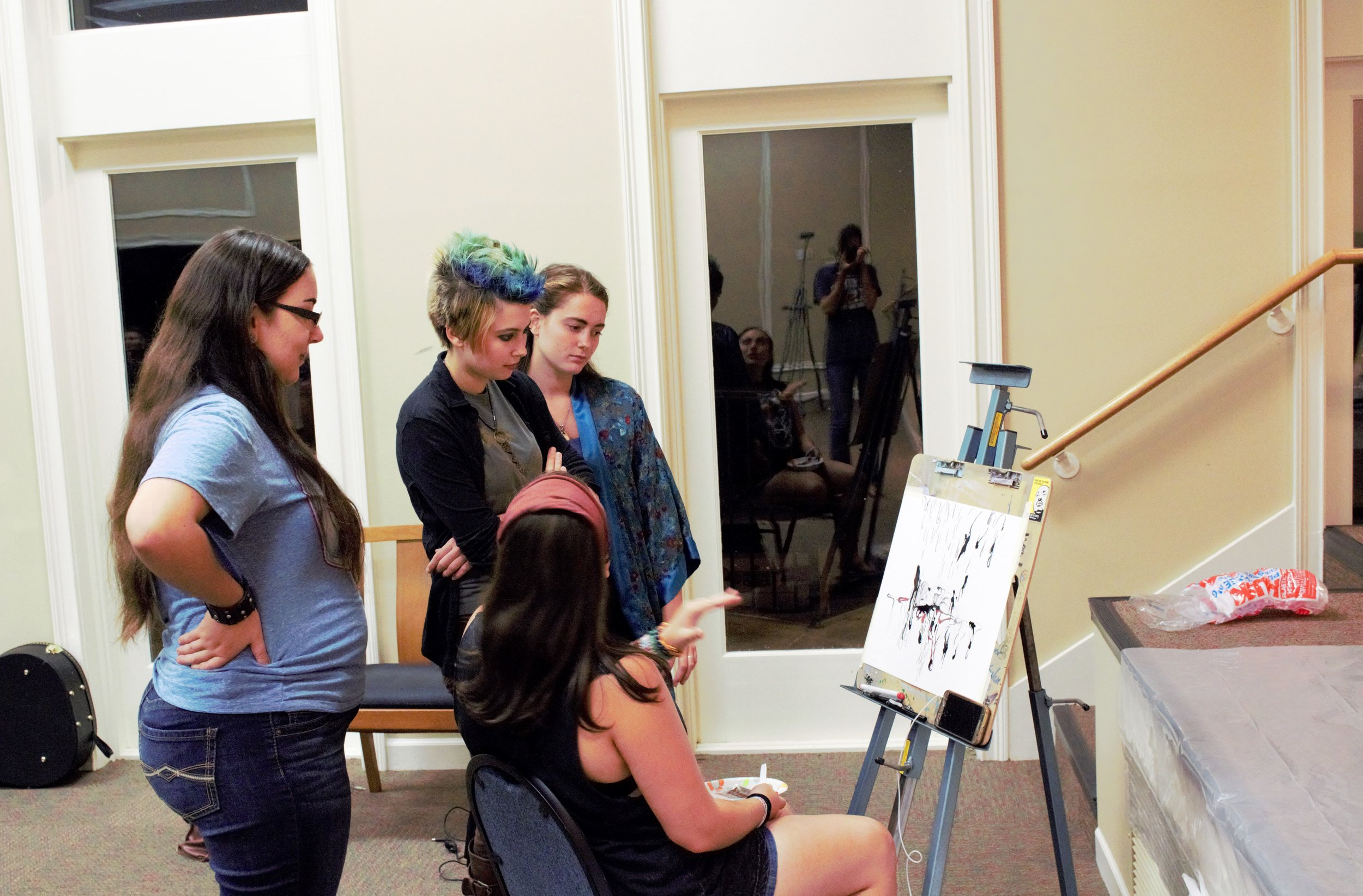 Students talk and discuss with Kat Fricault about her marker-made drawing.