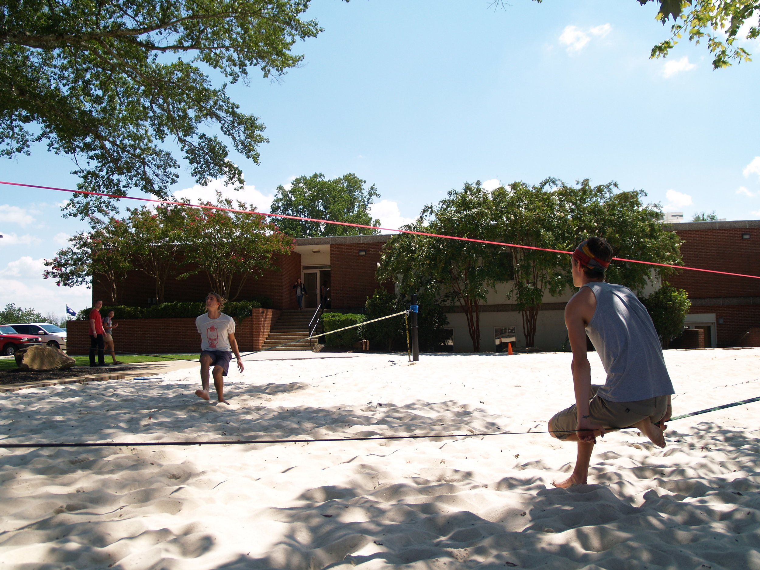 Students relax and enjoy the new slack lining area on a sunny afternoon.