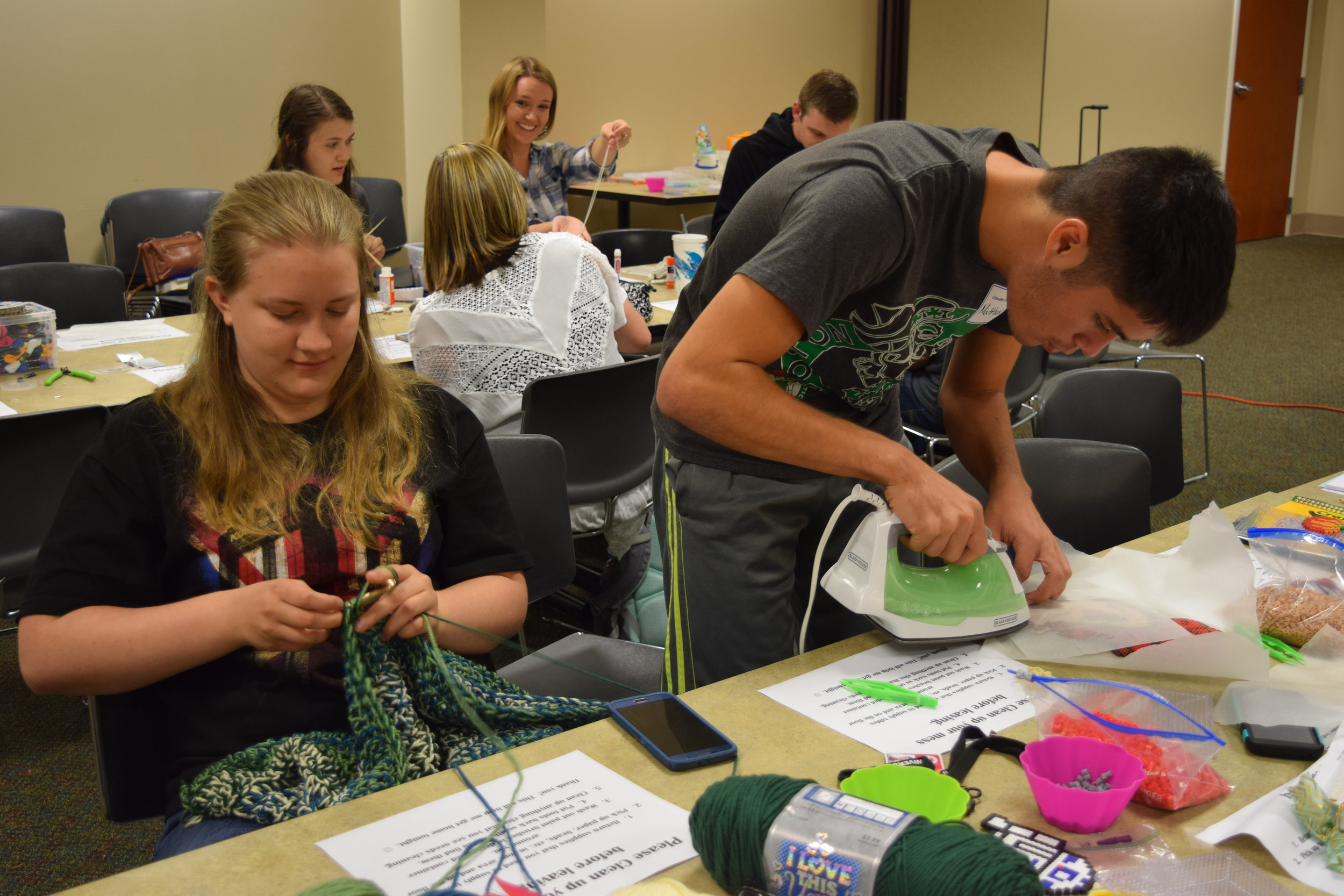 Jocelynn Johnson and Matthew Dunlap diligently work on their projects at the Crusader Craft Club.