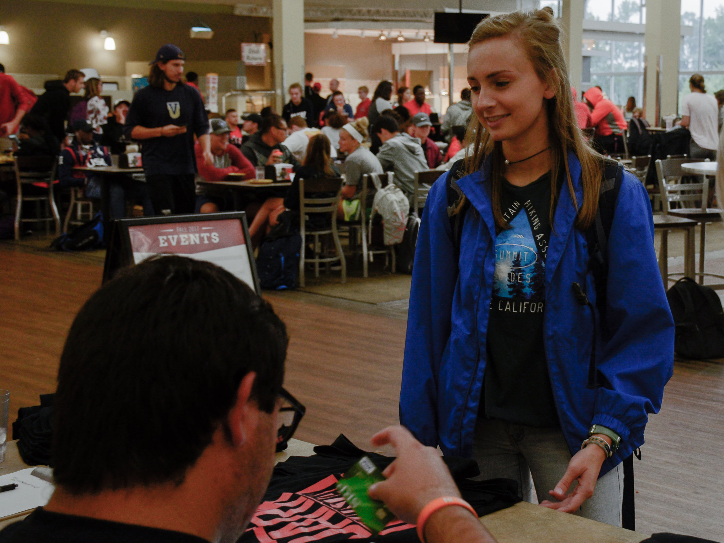 """Sophomore Sarah Bishop supports the NGU football team during lunch Thursday (August 31) afternoon as she buys a """"Dark Thursday"""" T-shirt in the cafeteria before the first game of the season."""