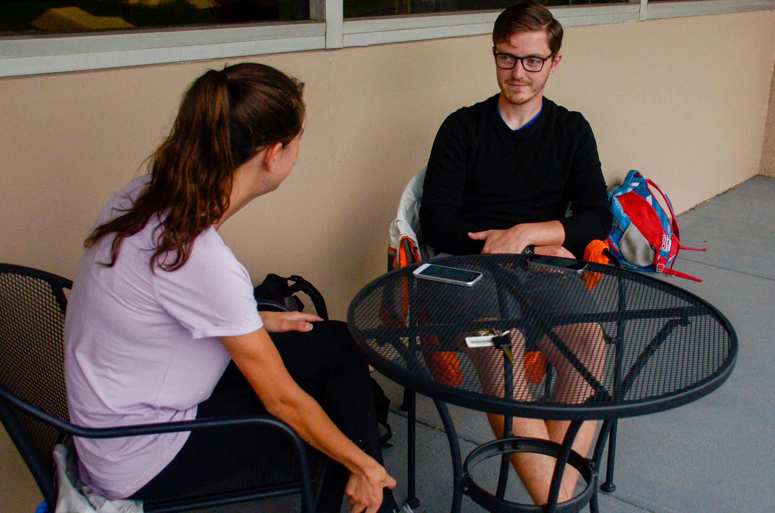 Ty Gautier, senior, catches up with his friend, Erin Leggett, as they relax and chat outside of the library.