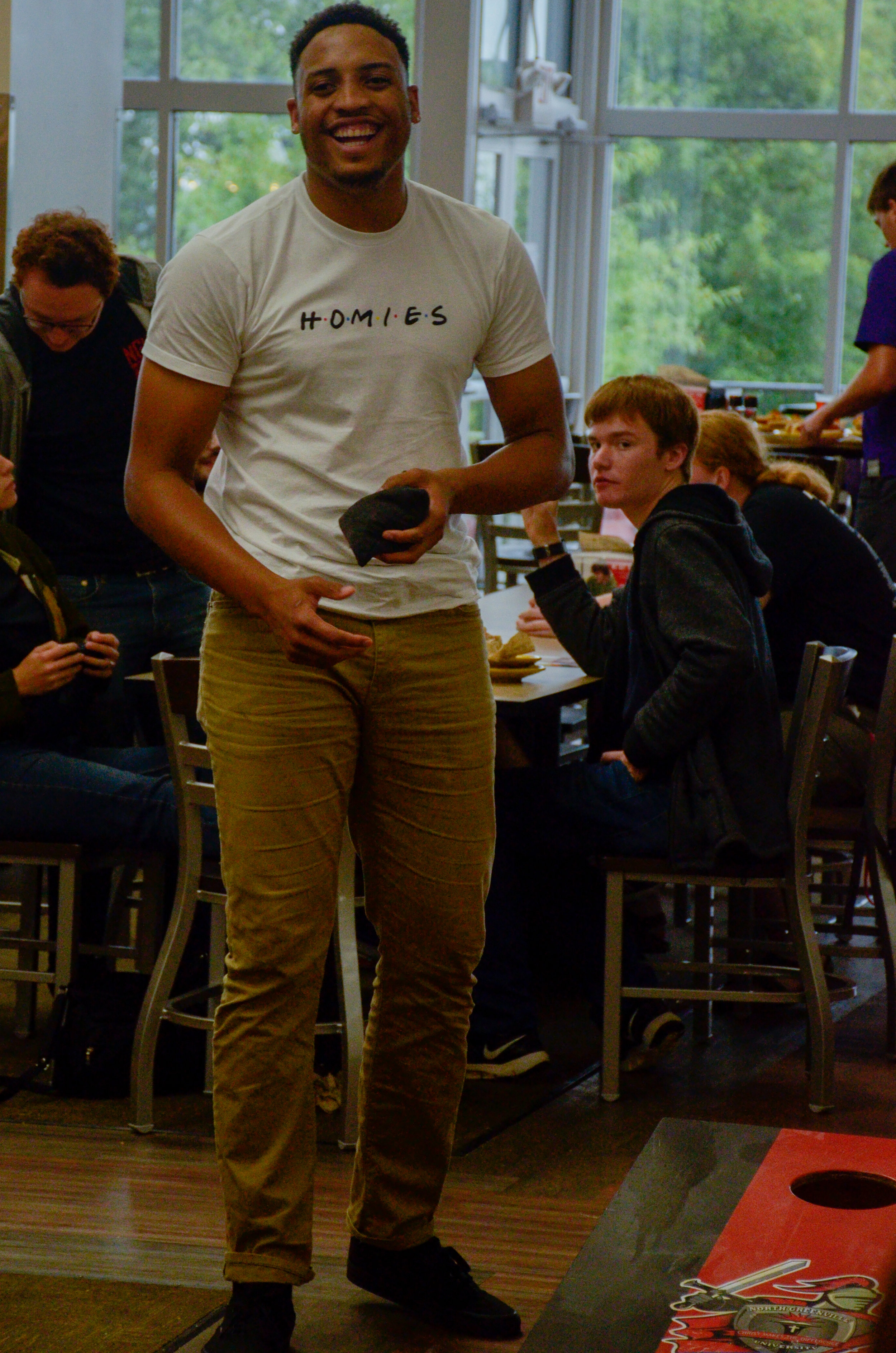 Chris Taylor, junior, gets his mind off of classes while playing Corn Hole in the cafeteria during a tailgating party before the football game on Thursday.