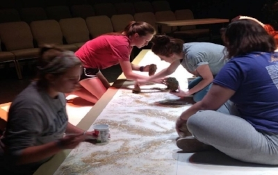 Scenic designer Tori Sheriff paints the set with theare practicum students.   Source: DeAndra Watkins
