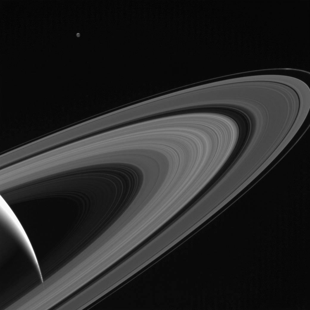 """4.  """"Saturn-lit Tethys""""   The sun beautifully reflects off Tethys' rings, another one of Saturn's moons."""