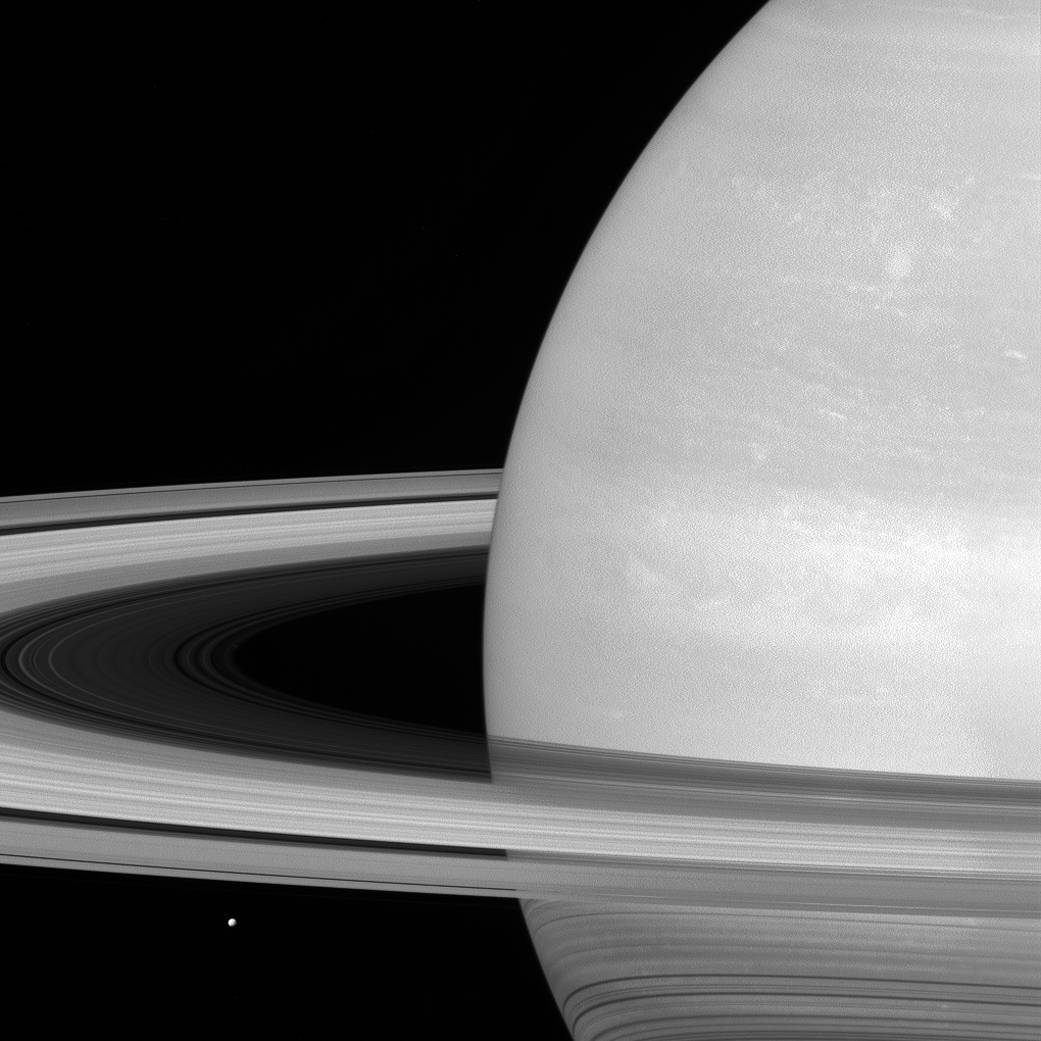 """6.  """"Tiny Mimas""""   Mima, characterized by its covering in ice, rests beneath Saturn's rings."""