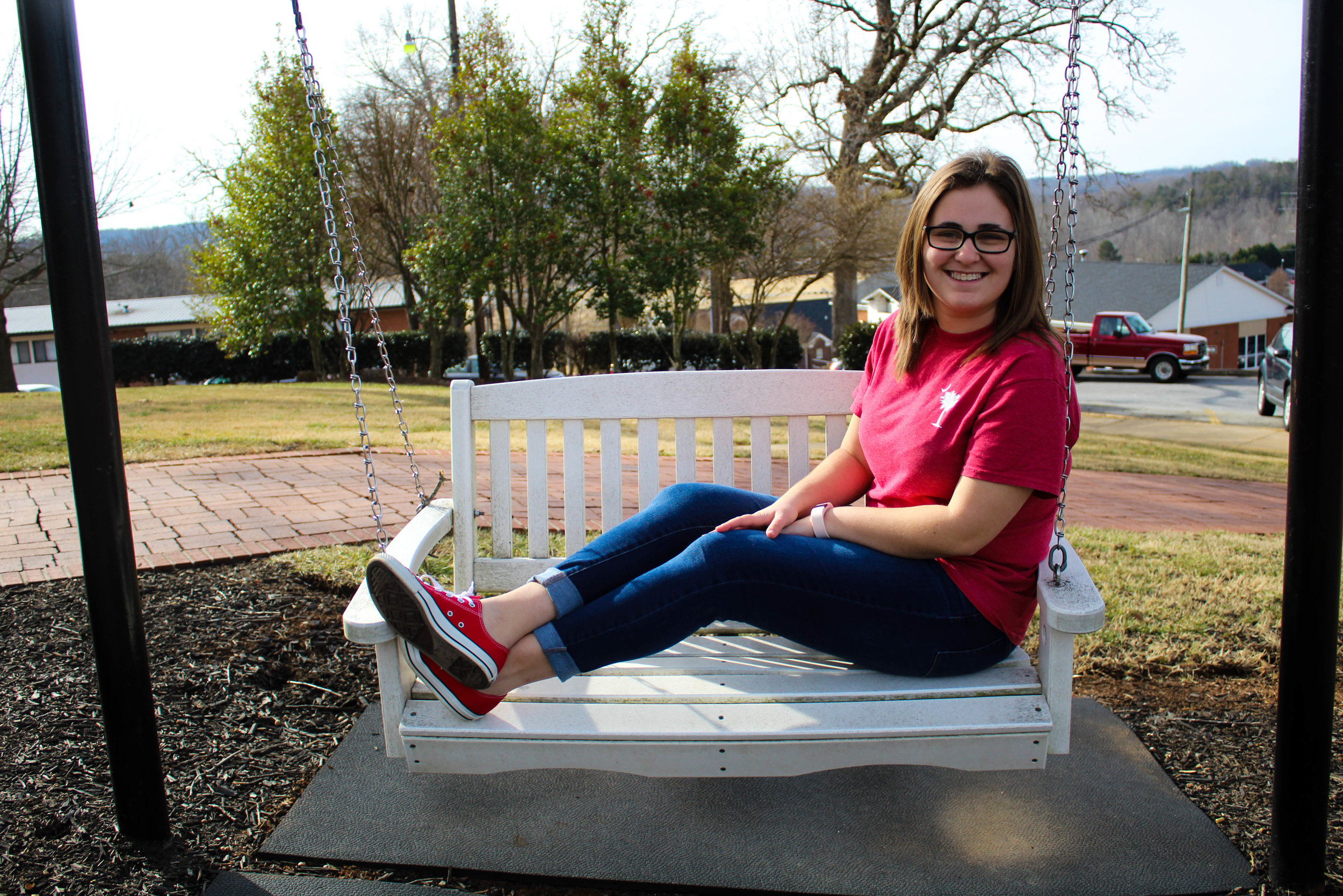Marissa Holst, a freshman early childhood education major, exhibits her encouragement for the awareness of heart disease by wearing red as she swings outside of Neves.