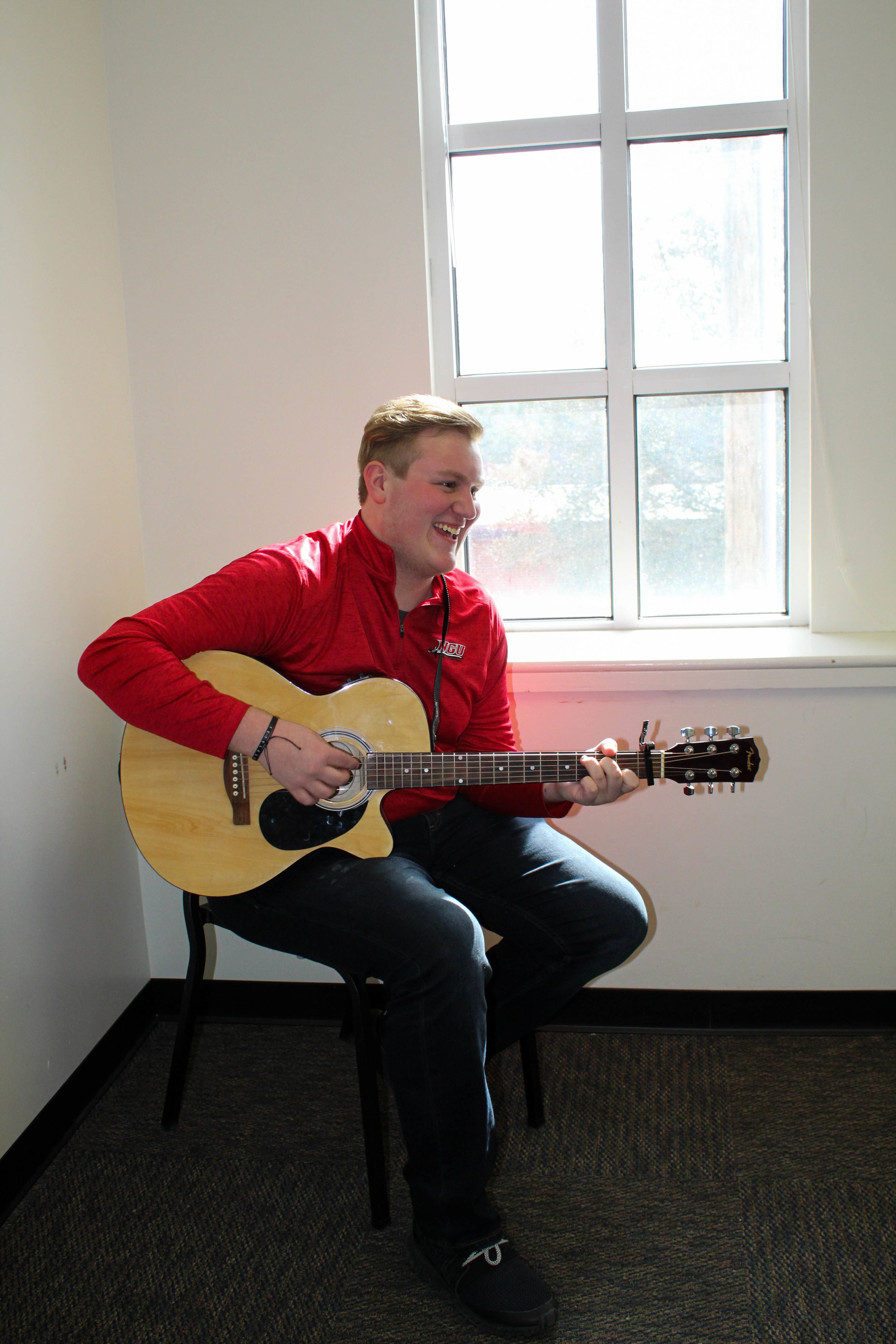 Nicolas Olson, a freshman double major in business administration and Christian studies, practices his guitar as he wears red for the awareness of heart disease.