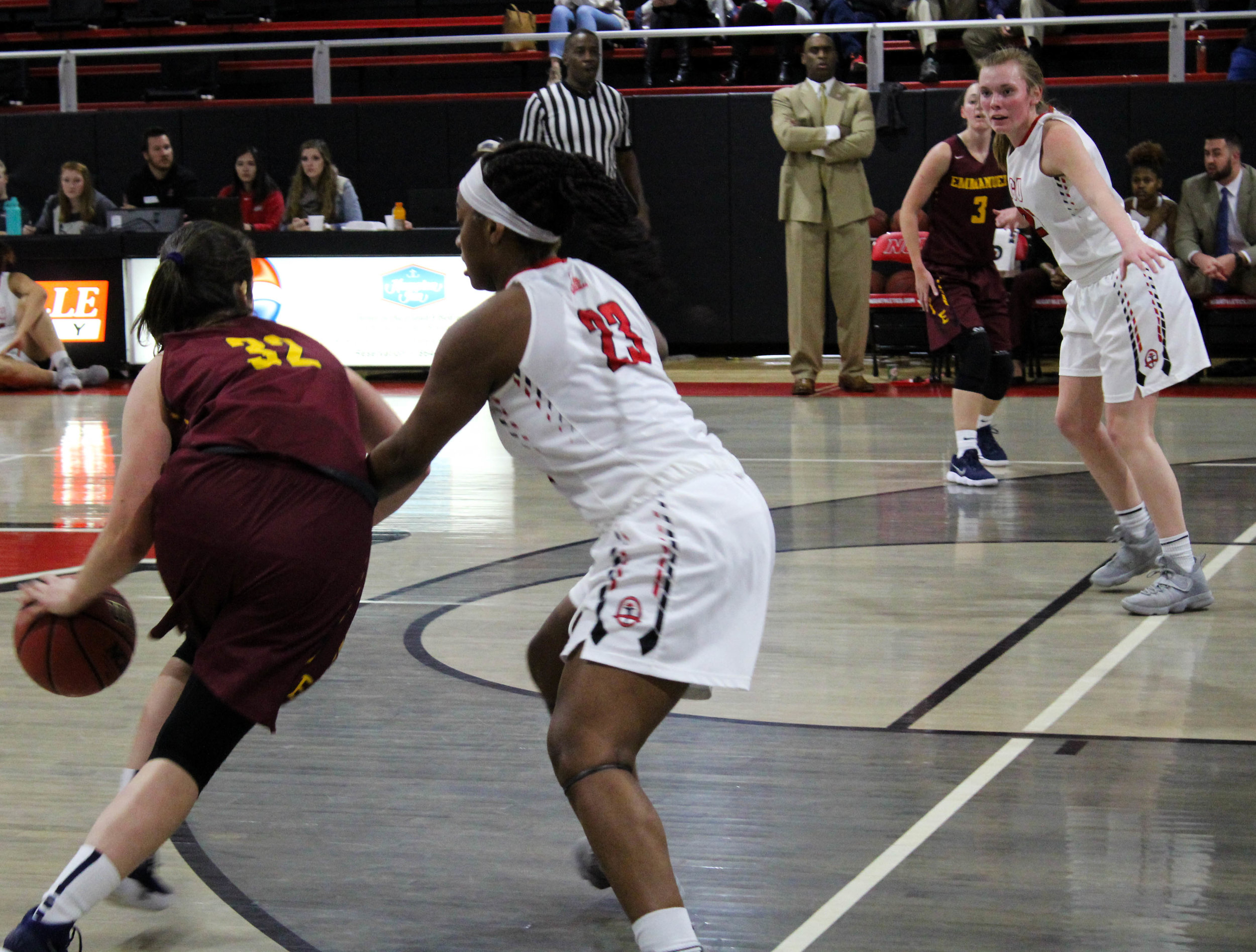 Tyana Sanders (23) guards Emmanuel's point guard as she attempts to drive towards the basket.