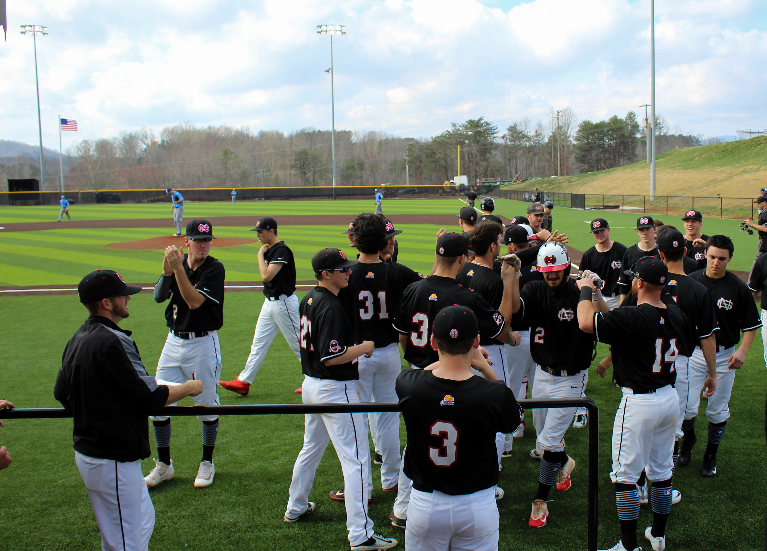The NGU Men's Baseball team cheer on Utah Jones (2) after hitting a home run.