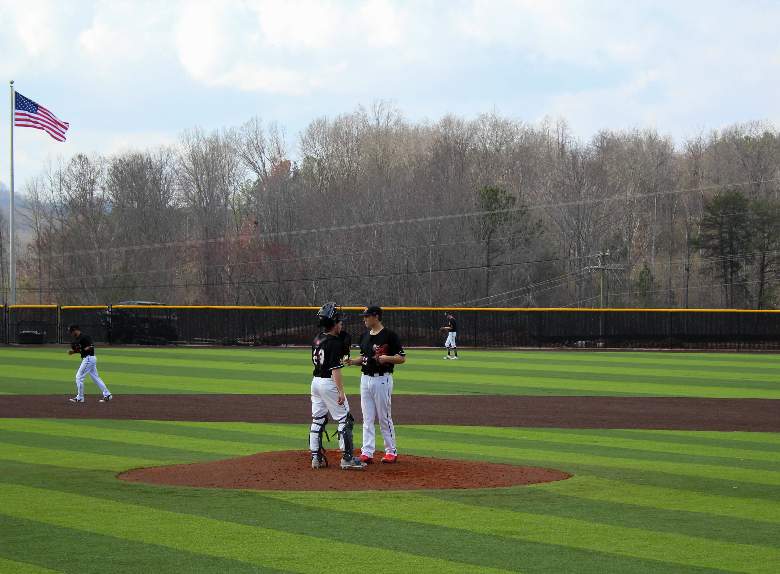 Lex Tuten (23) and Ethan Garner (27) talk on the mound about pitch strategy.