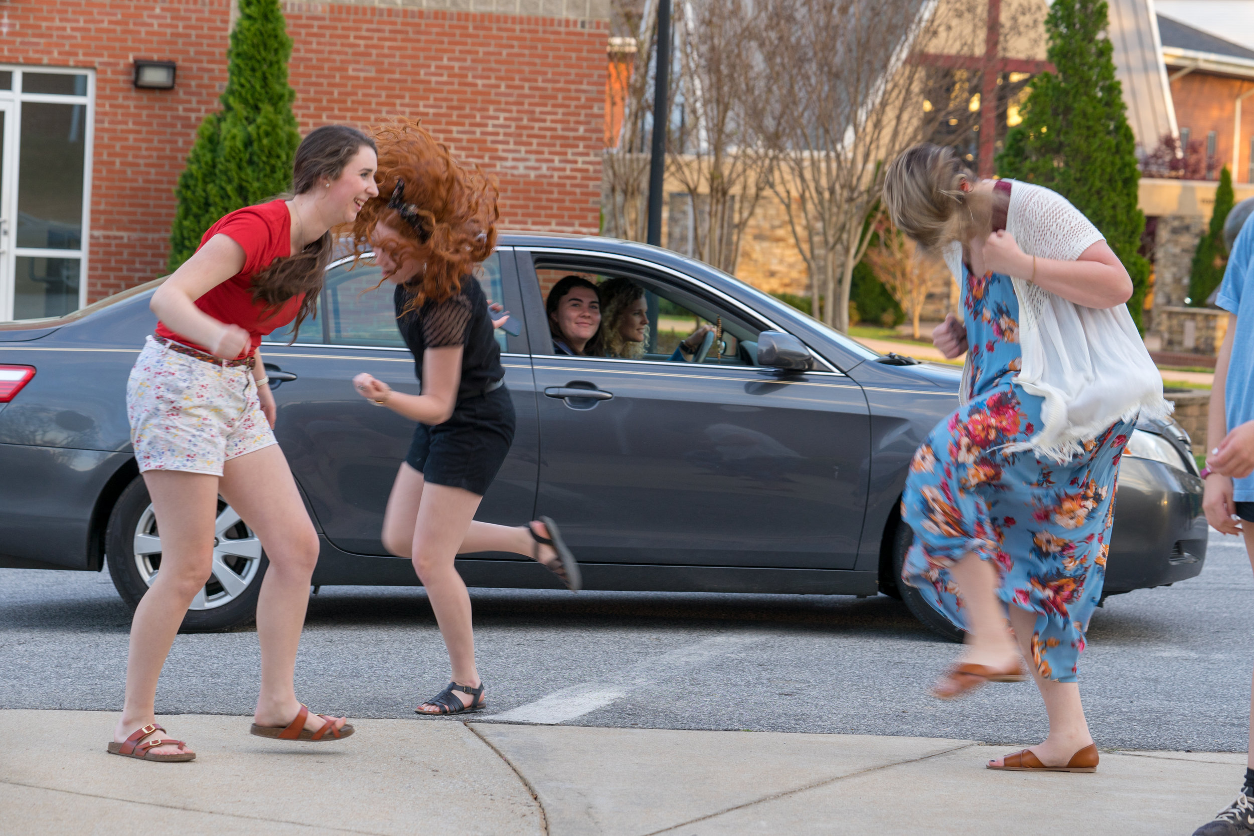 A group of NGU students dance like crazy as friends pass by jamming out.