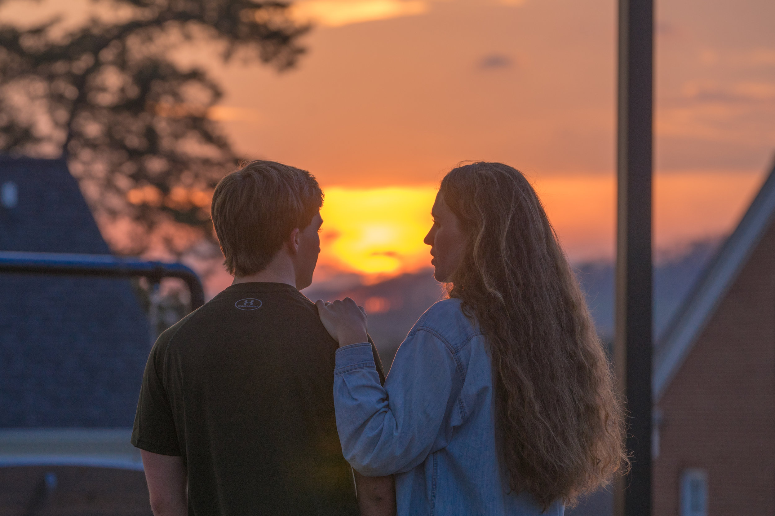 A couple takes in a peaceful moment as the sun sets behind the Blue Ridge mountains.