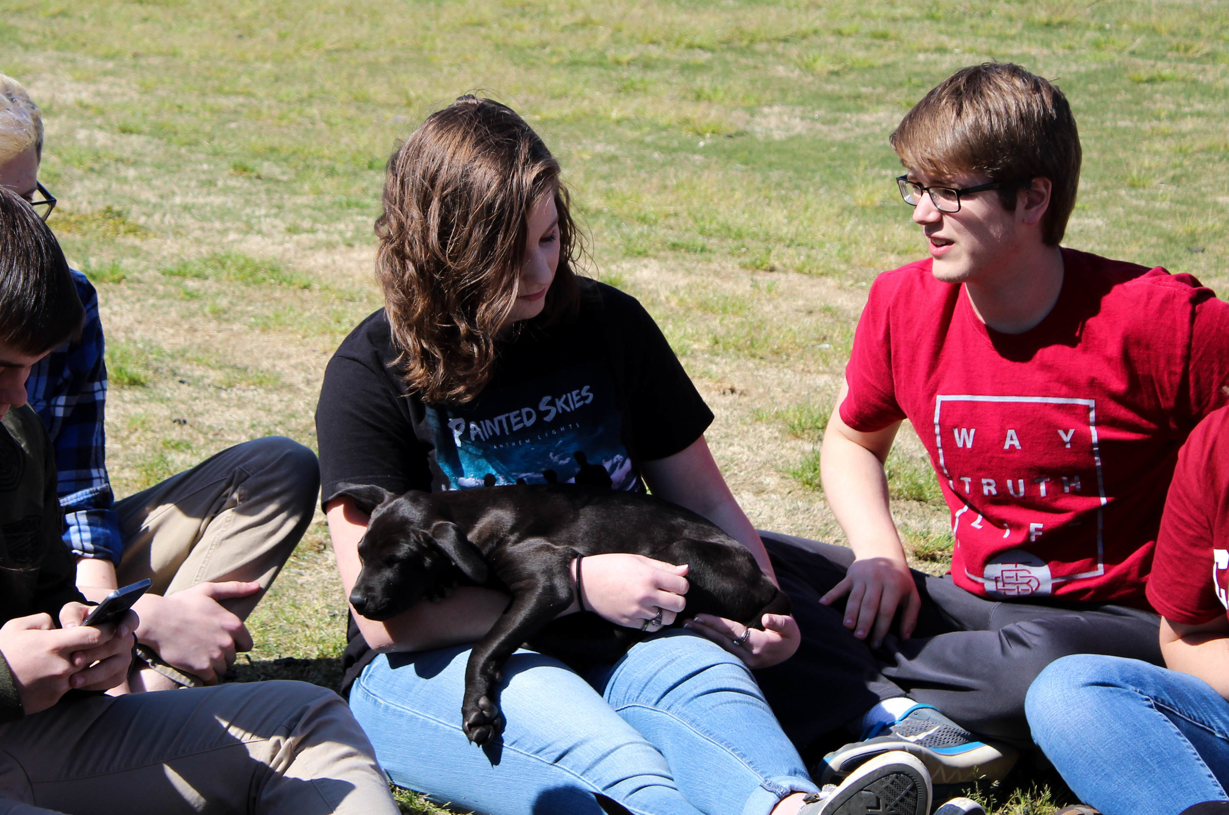 Freshman Naomi Schaaf holds a puppy as it takes a nap.