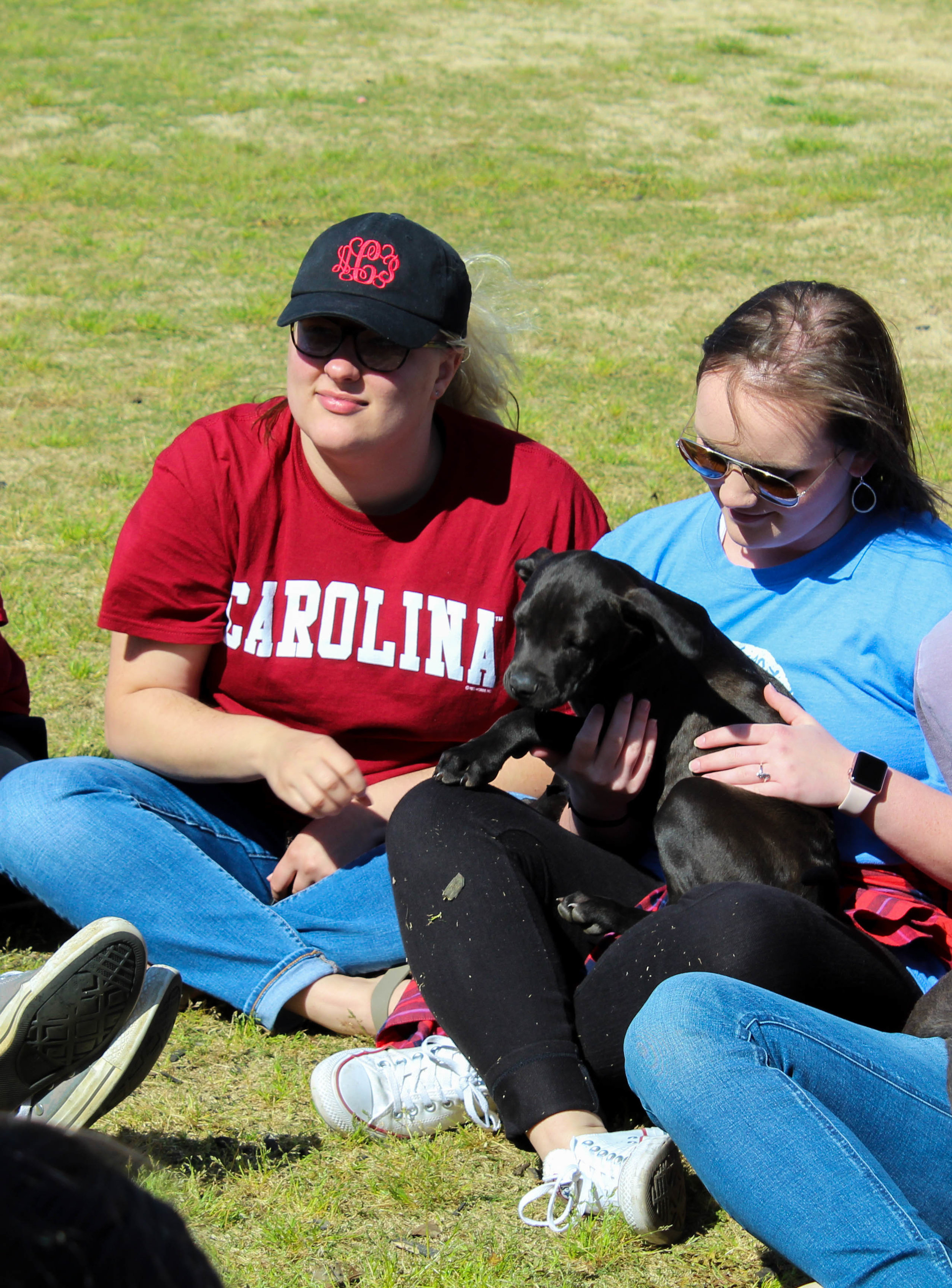 Freshman elementary education majors Allison Cantrell and Parker Foster pet a puppy.