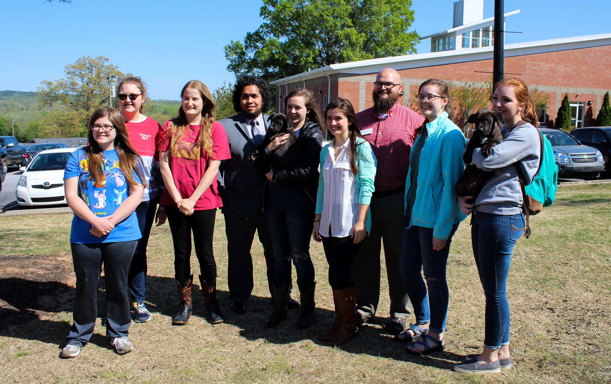 The Animal Science Club, who hosted the event, get together with some puppies to take a picture.