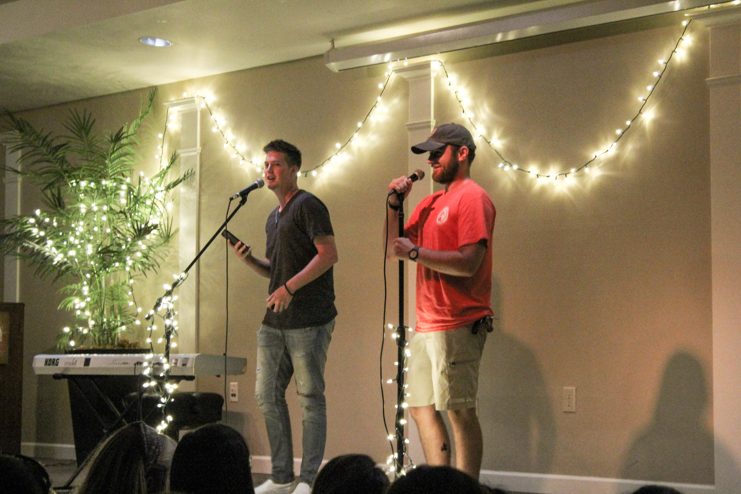 Seniors, Taylor Brunson and Jon Fordree, also the announcers of the coffeehouse, make jokes to keep attention on the stage as the next act makes their way to the stage.