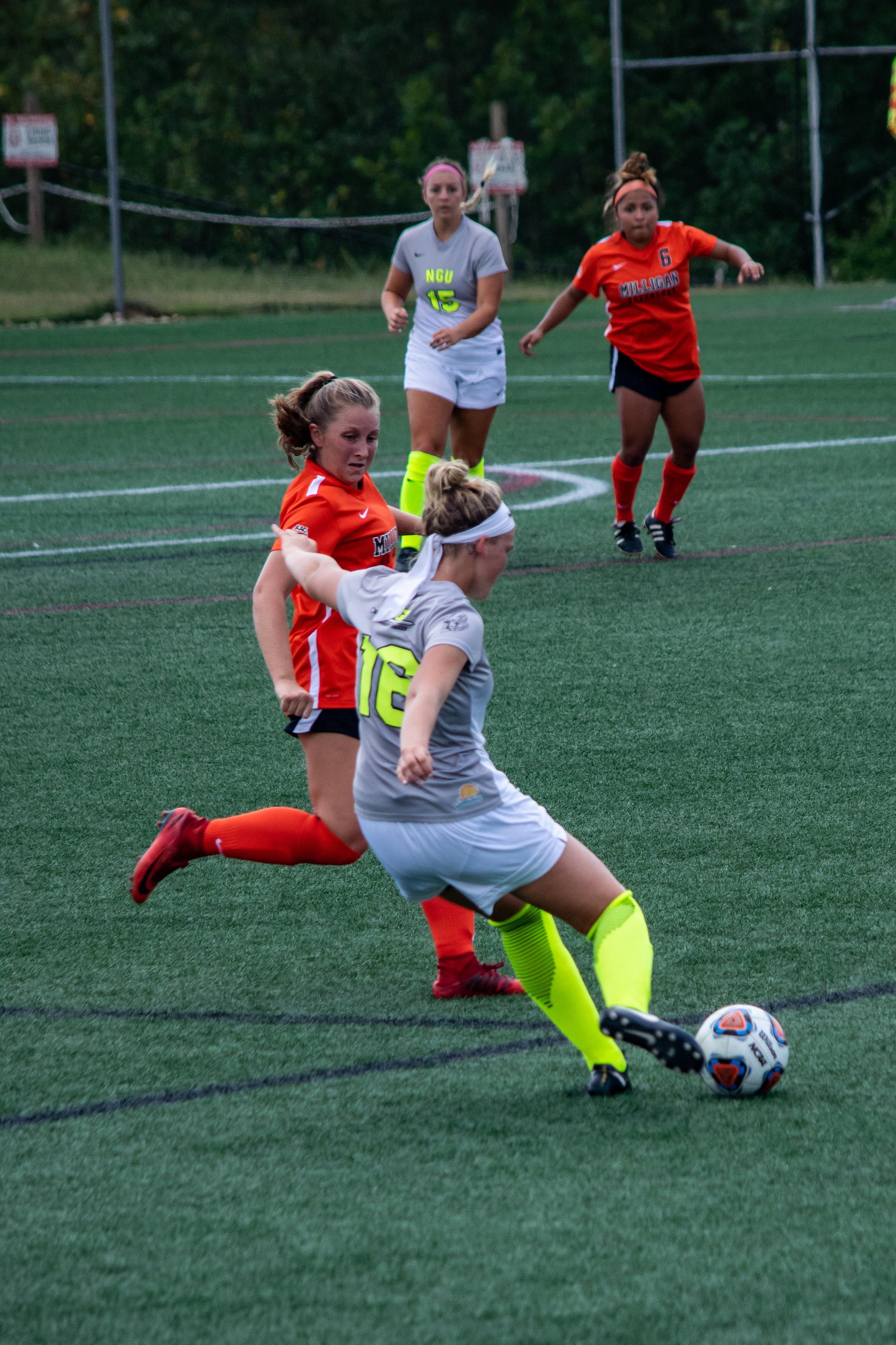 #16 Michaela Gleed prepares a strong kick to pass the ball to team member #15 Mackenzie Neff.