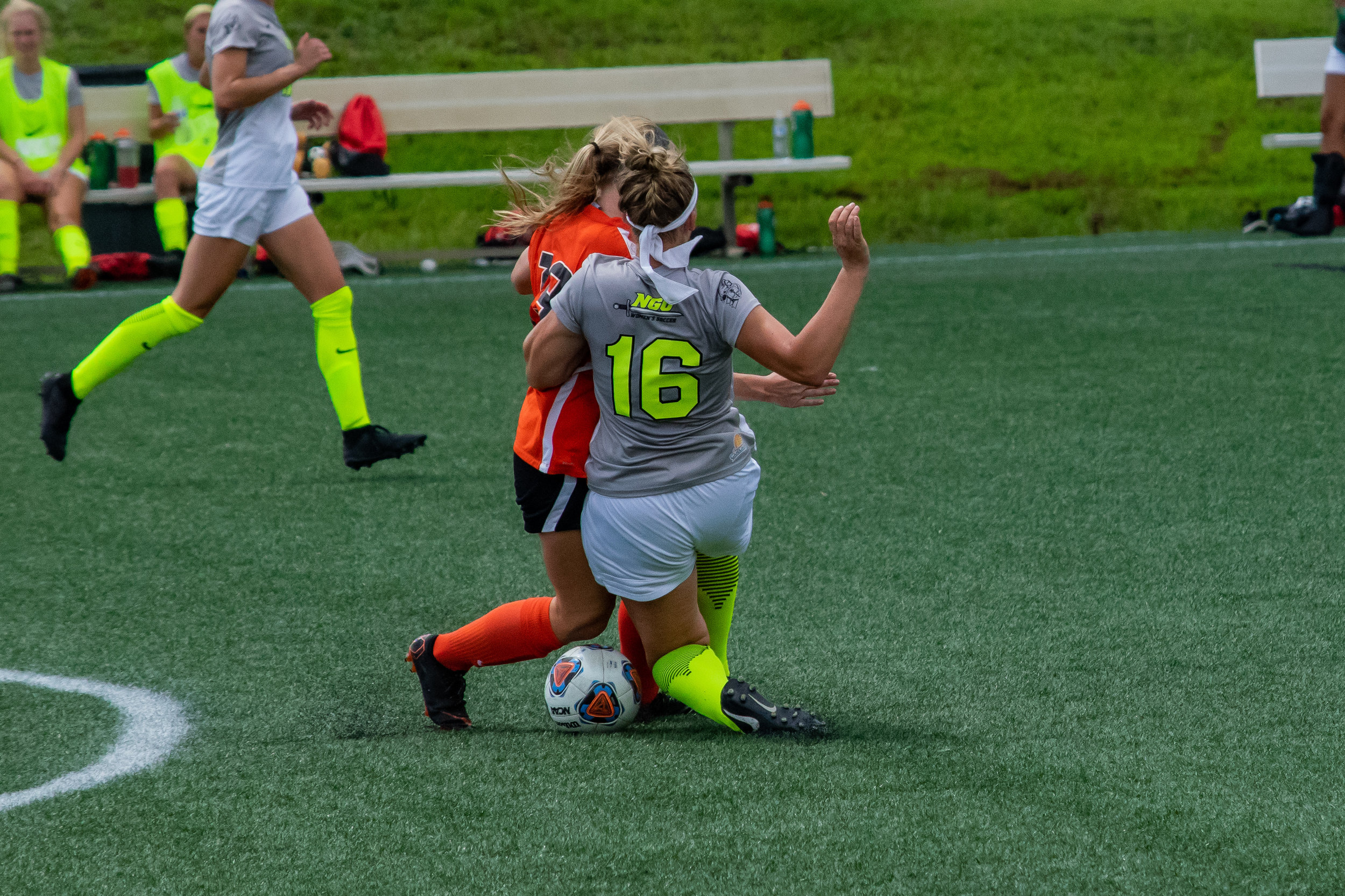 #16 Michaela Gleed runs into the opposing player trying to pass the ball to a team member.