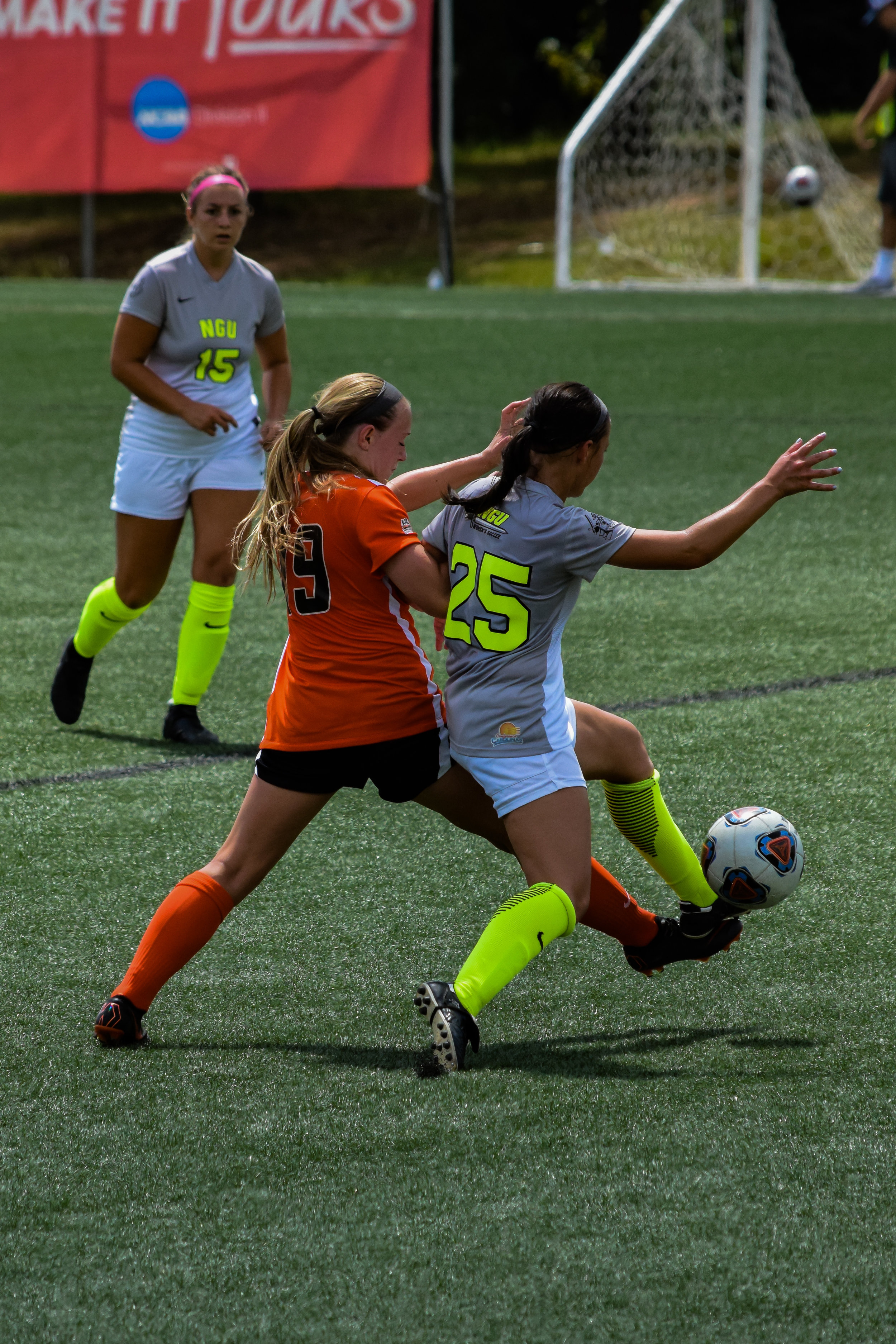 #25 Natalie Johnson risks falling as she goes to pass the ball to her teammate as #15 Karly Denaburg runs to help.