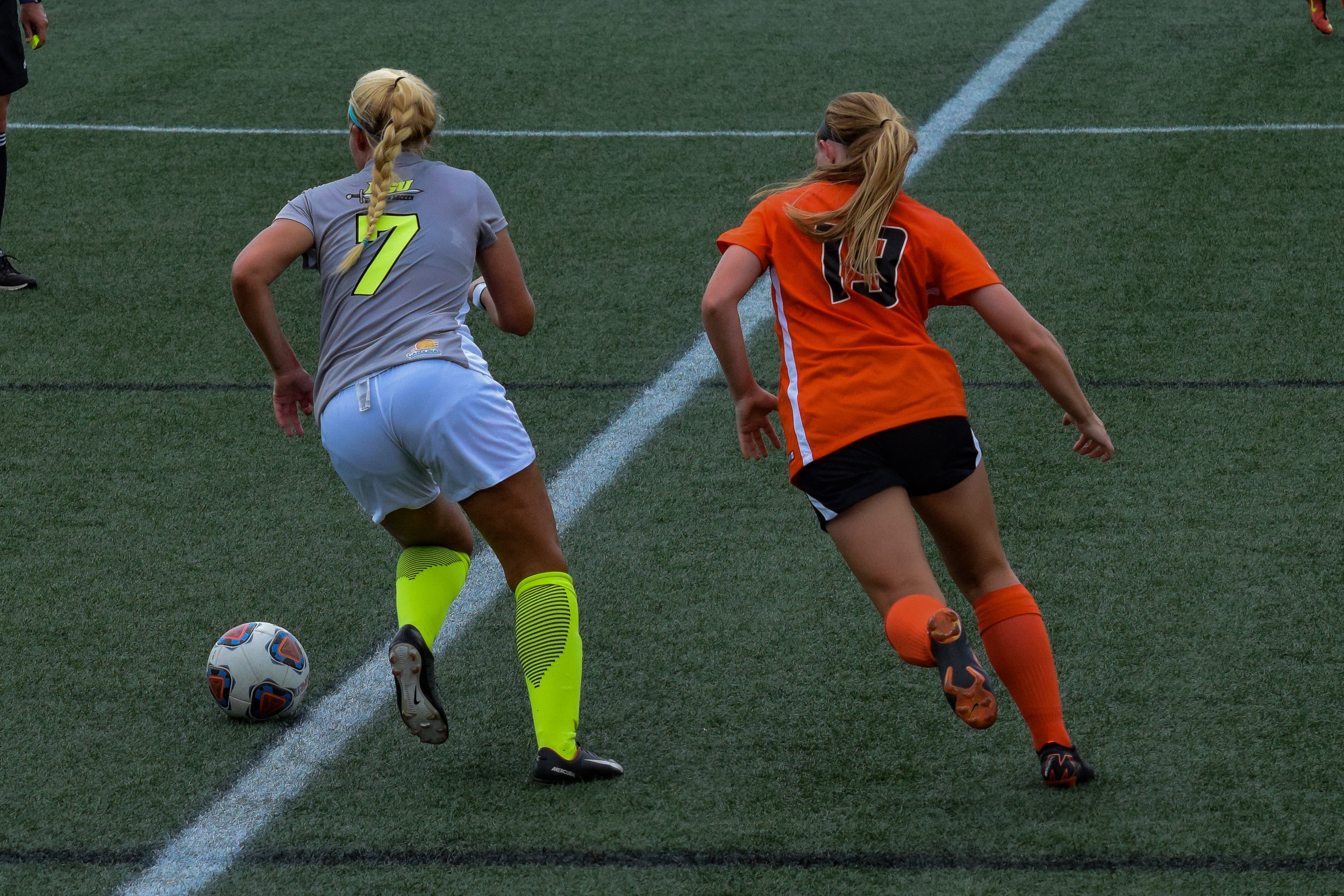 #7 Abby Robinson begins to run the ball back to the opposite side of the field to attempt to make a goal.