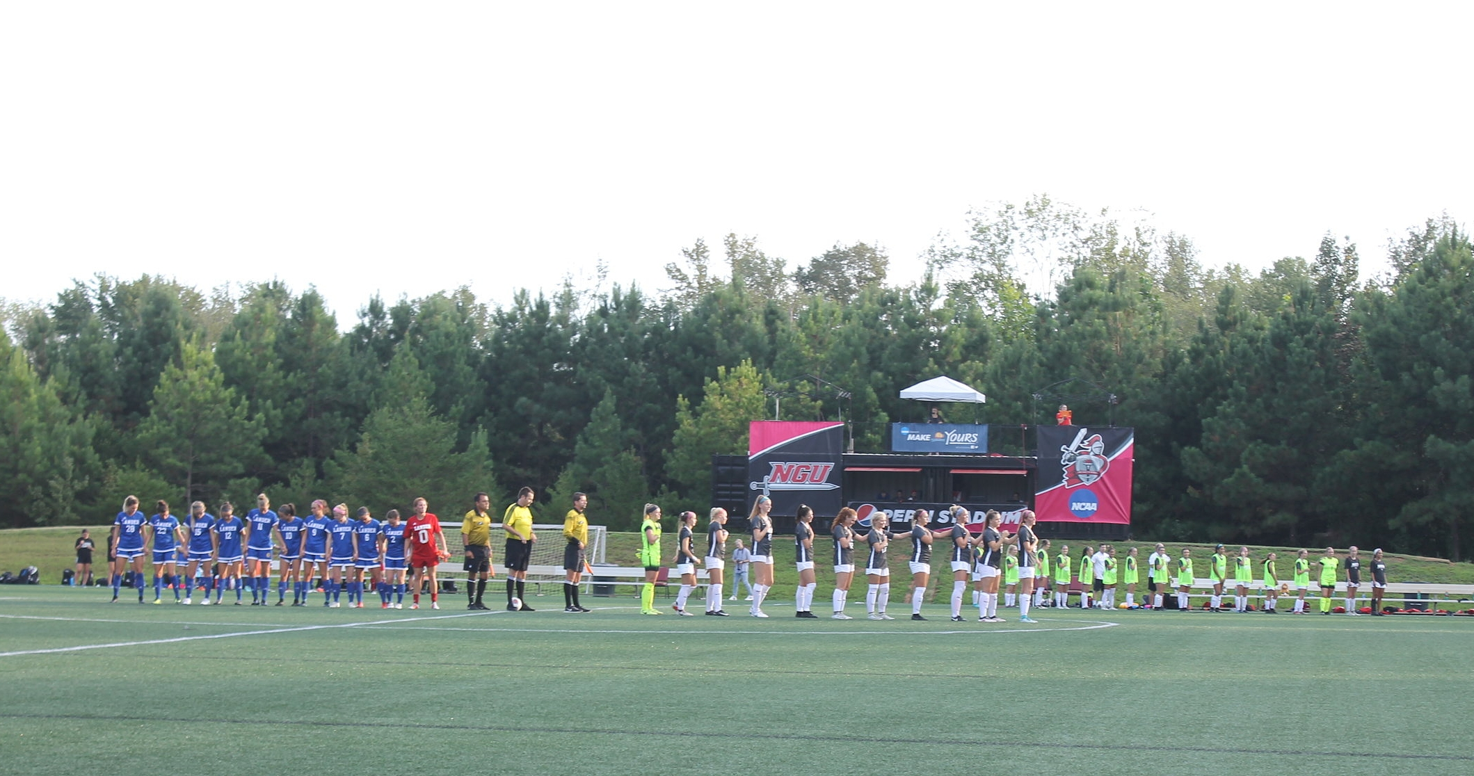 Both teams standing together for the pledge of allegiance.
