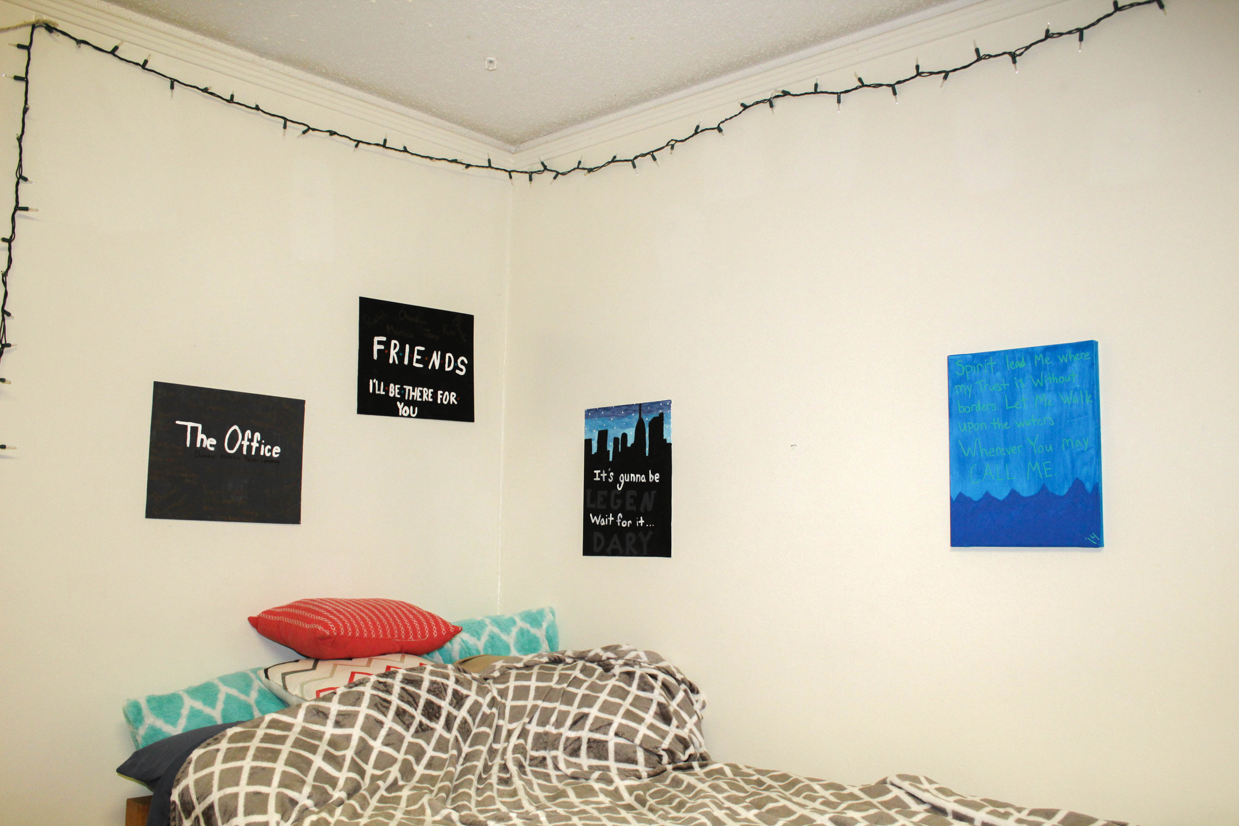Kayla Gibson, senior, shows her love for multiple TV shows by hanging painted canvases in her room displaying their titles.