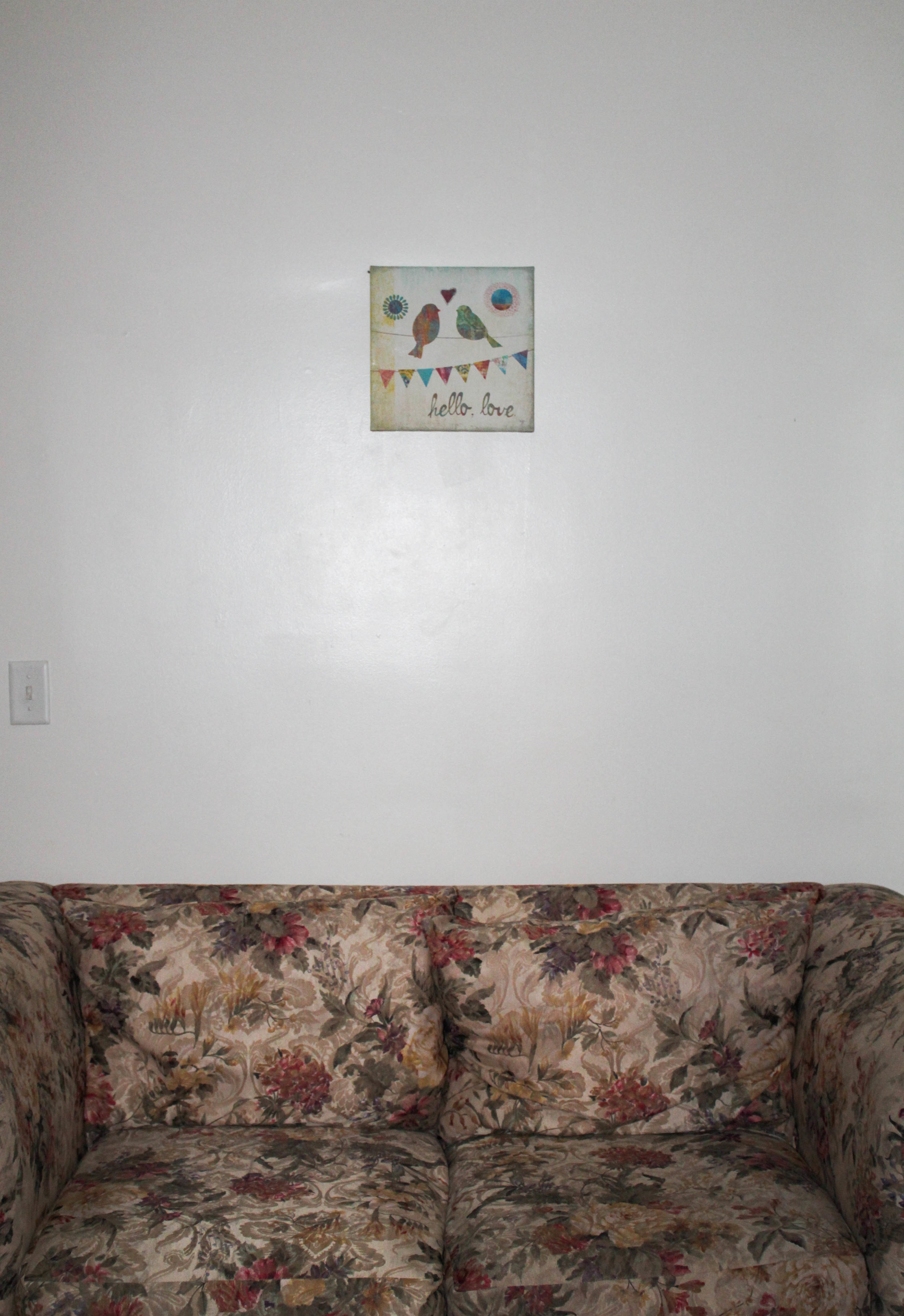 In a house on campus, the girls have a couch and wall art to make the room feel more like home.