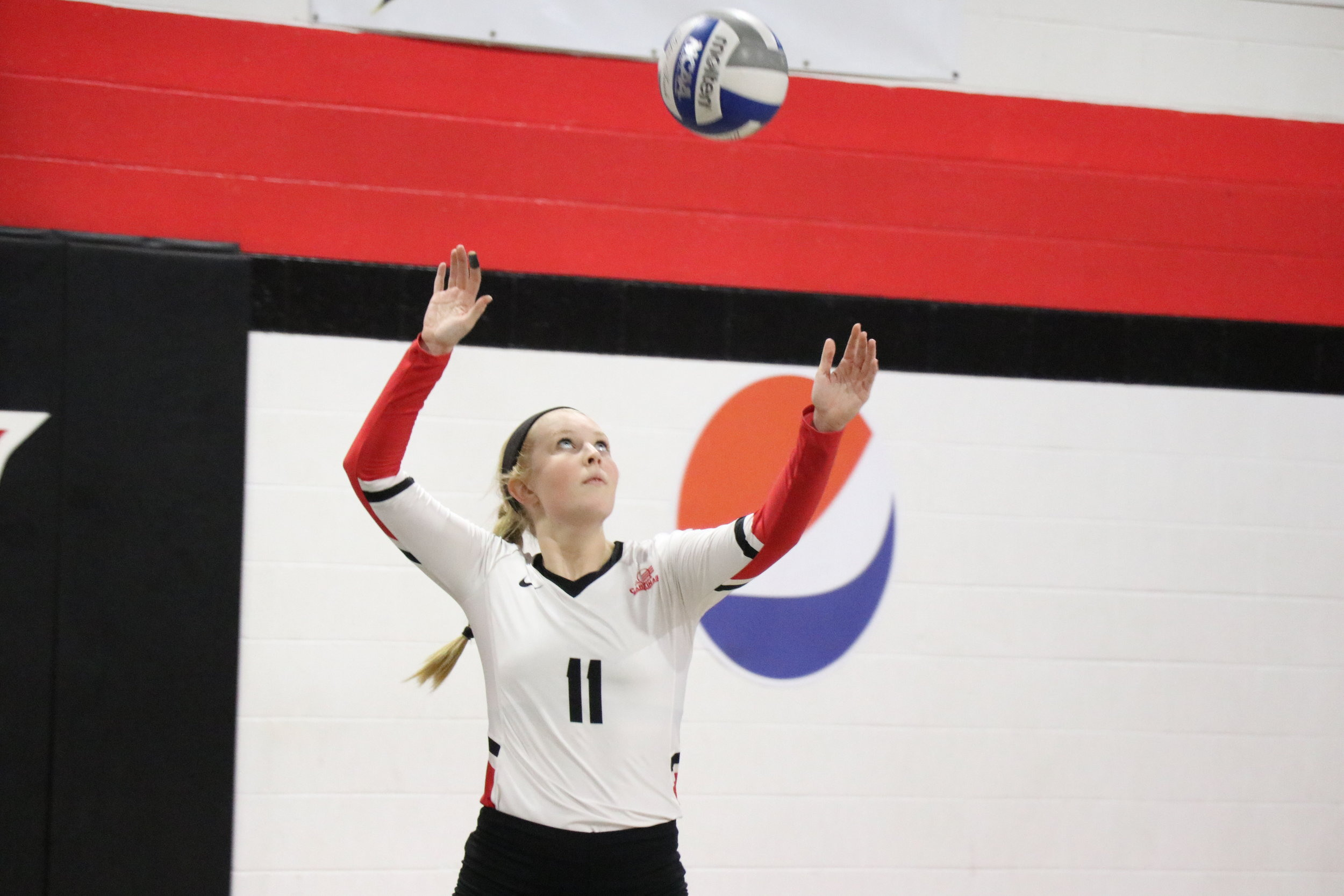 Junior, Madison Curtis serves the ball to the other team.