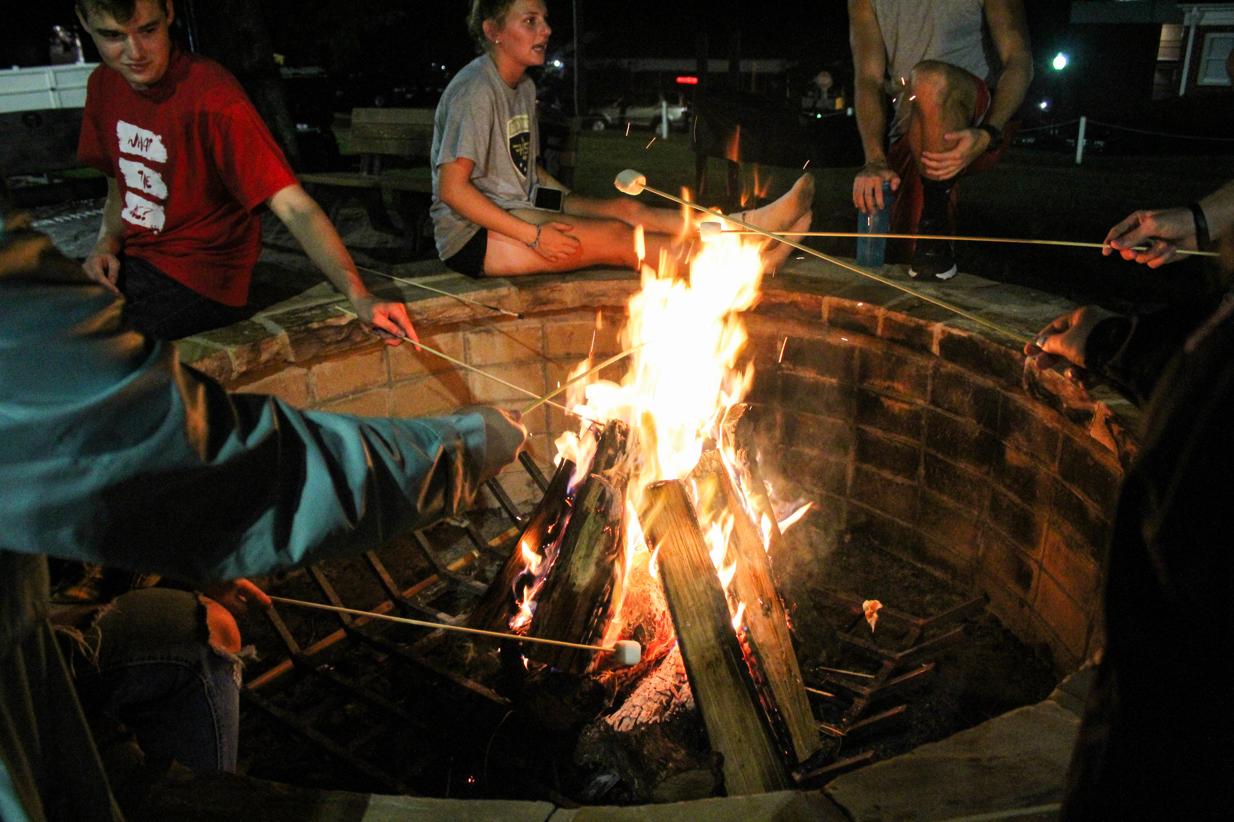 Students gather around the fire pit and roast marshmallows to make s'mores while the watch the volleyball tournament.