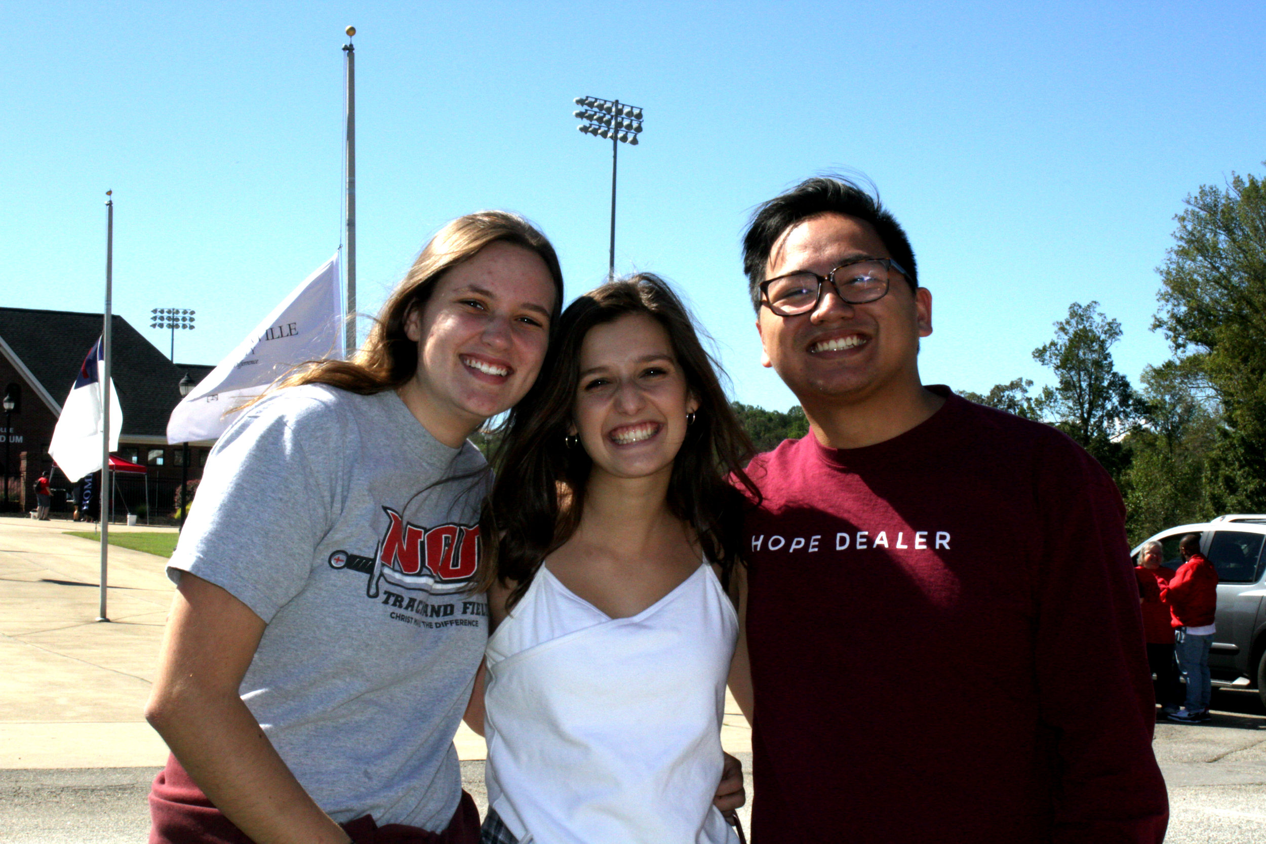 From left to right, students Caroline Smith (Sophomore), Abbey Blackwood (Senior) and Kieffer Mendoza (Alumni) enjoy the tailgate as they wait for the parade to start.
