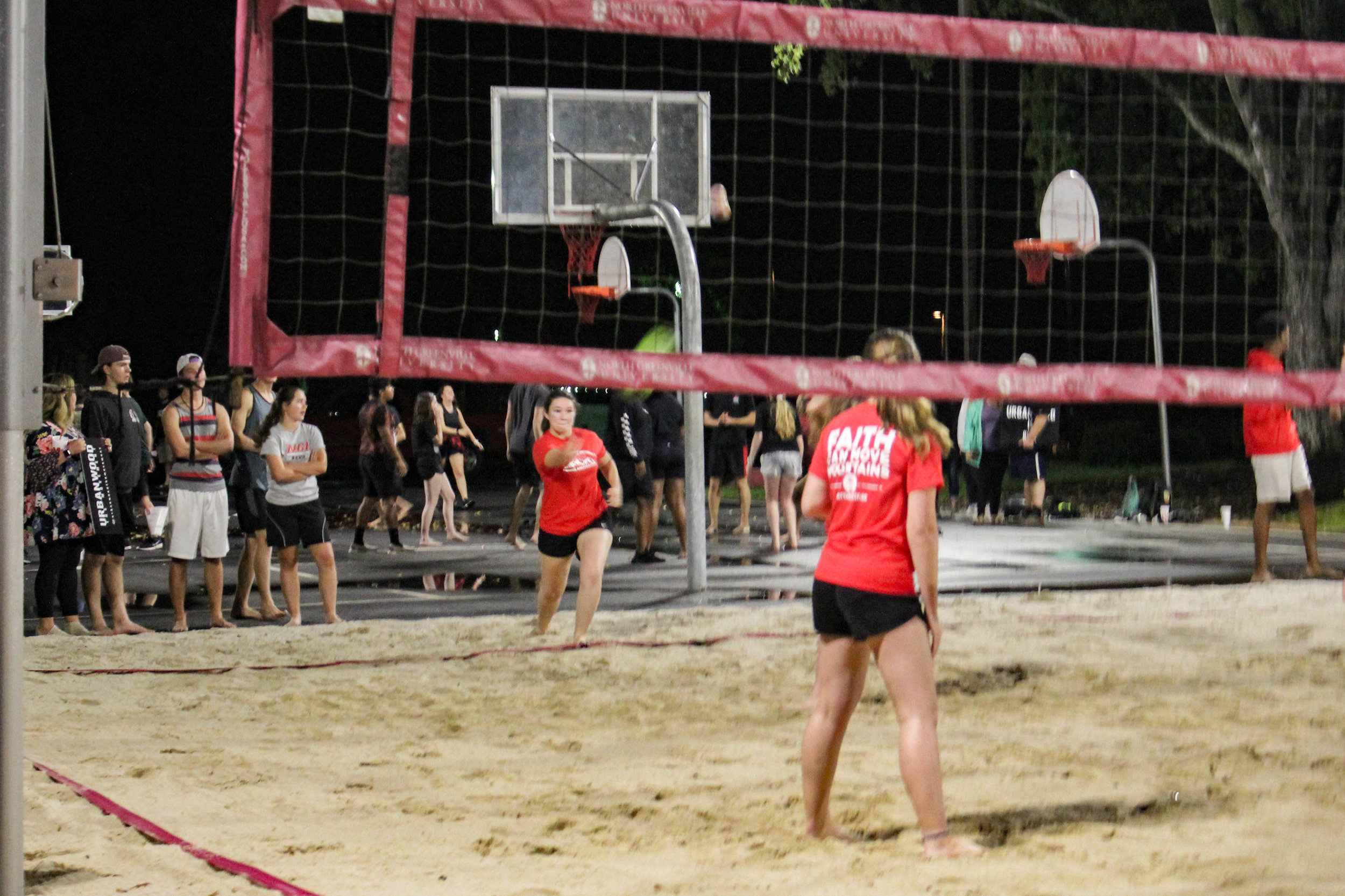 While playing against the animal science club, a member of the campus ambassadors serves the ball.