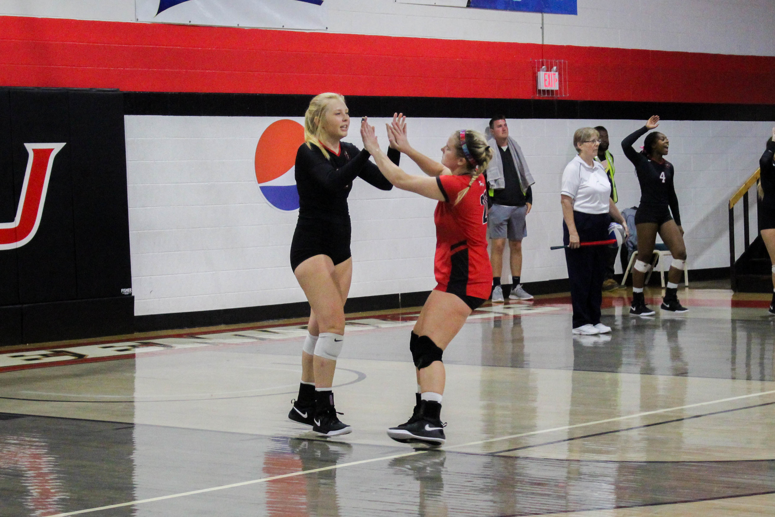 Freshman Whitley Kahler (20) congratulates senior Sara Miller (11) after Miller served a ball that resulted in a point for NGU.