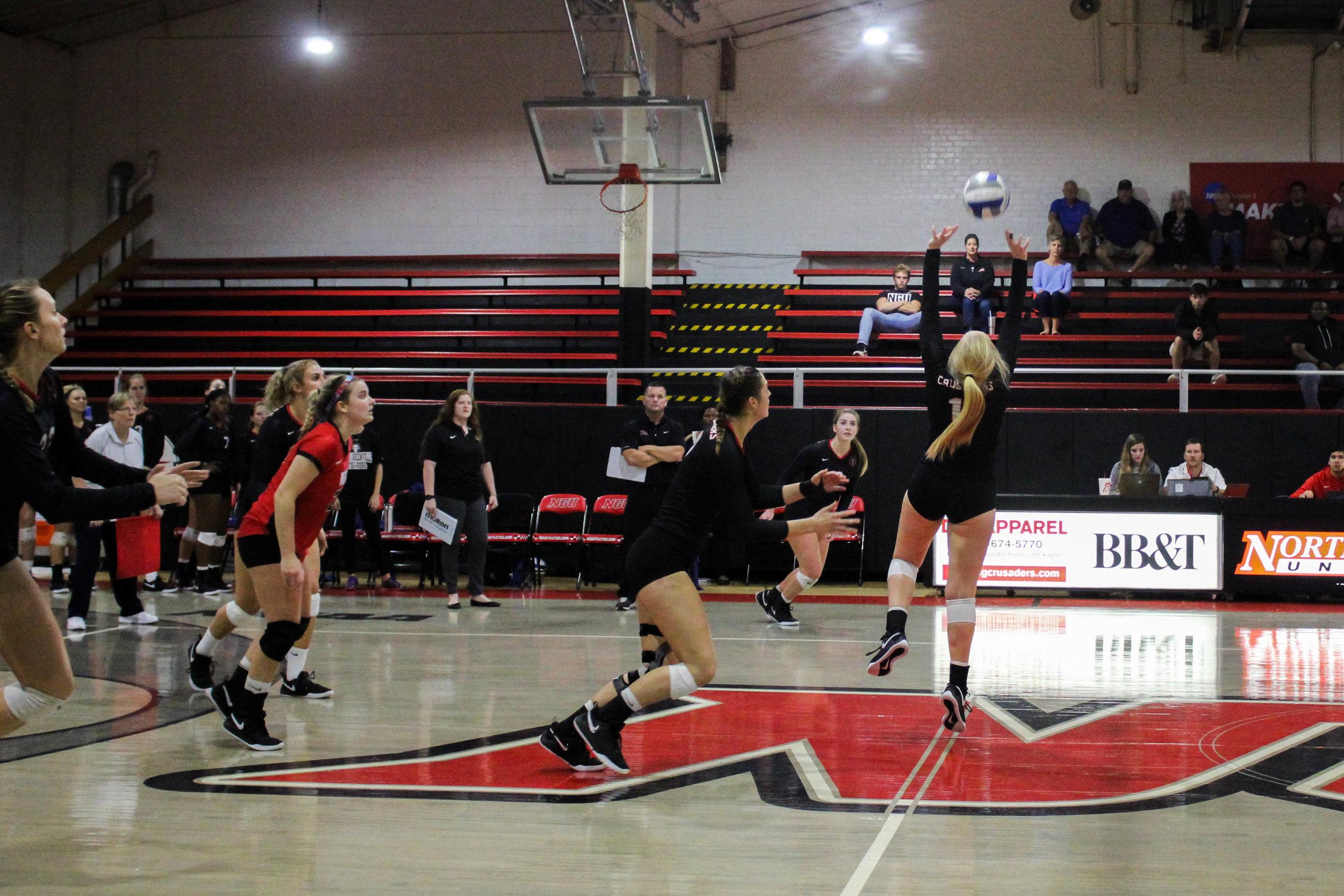 Senior Annie Beisecker (17) runs forward as she prepares to hit the ball set up by senior Sara Miller (11).